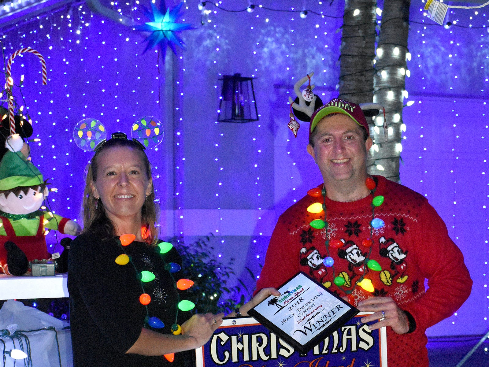 Winners Suzi and Eric Szczepinski display their hard-won yard sign after their home was determined the winner of the annual Christmas Home Decorating Contest on Friday night.