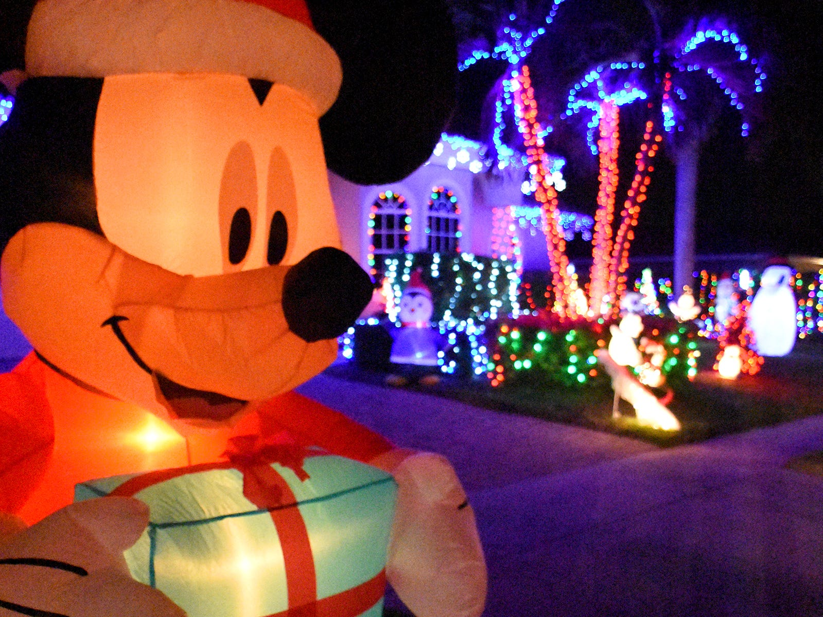Inflatables complement a house and its yard lights during the judging of the annual Christmas Home Decorating Contest on Friday night.