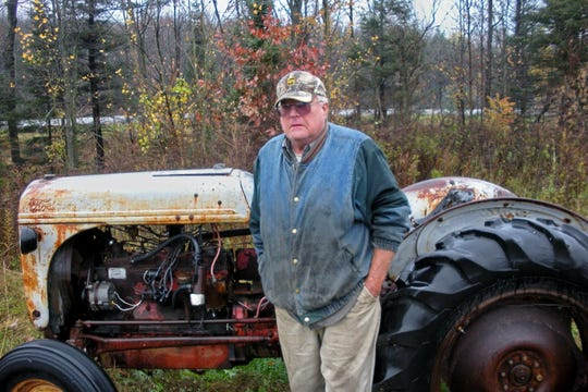 Roger Hoeppner in a 2014 photo, standing near a tractor he was restoring at his home in the Town of Stettin, near Wausau.