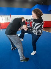 Reporter Karen Pilarski uses a knee kick to the chest to fend off a simulated attack by Precision Defense Training owner Chris Withrow during a training session at Fit Body Boot Camp in Brookfield on Monday, Dec. 17.