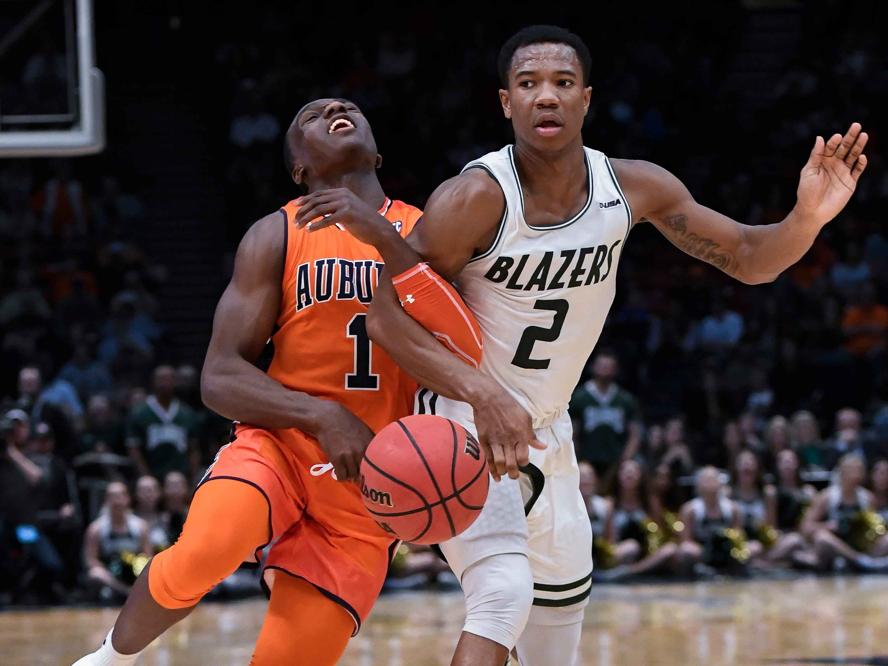 UAB guard Jeremiah Bell (2) fouls Auburn guard Jared Harper (1) during overtime on Saturday, Dec. 15, 2018, in Birmingham, Ala.