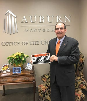 Carl Stockton, chancellor of AUM, holds up the new Alabama license plate that will honor the school.