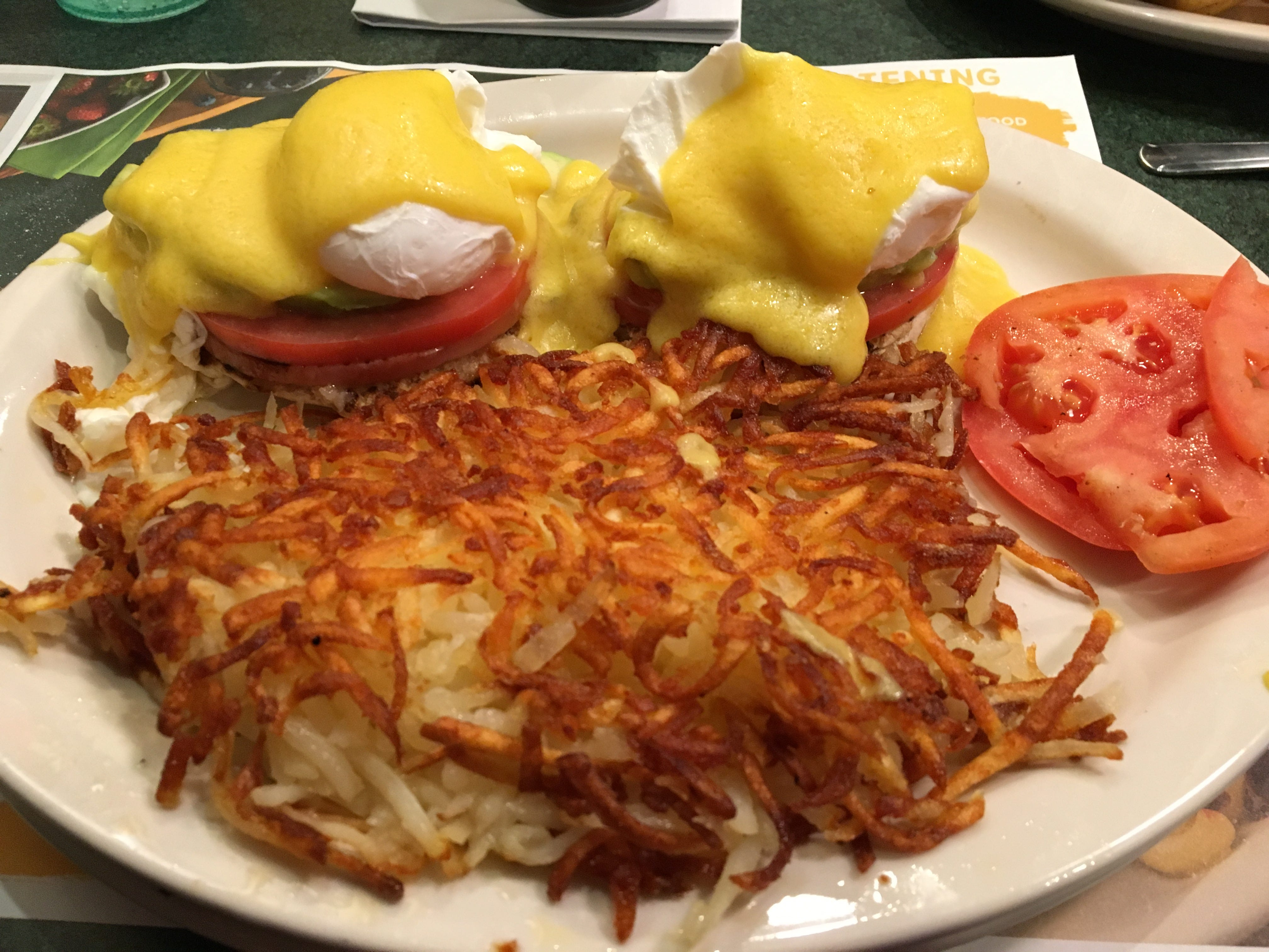 The San Francisco Eggs Benedict features fluffy poached eggs, avocado slices and tomatoes atop an English muffin, with hollandaise sauced drizzle over.