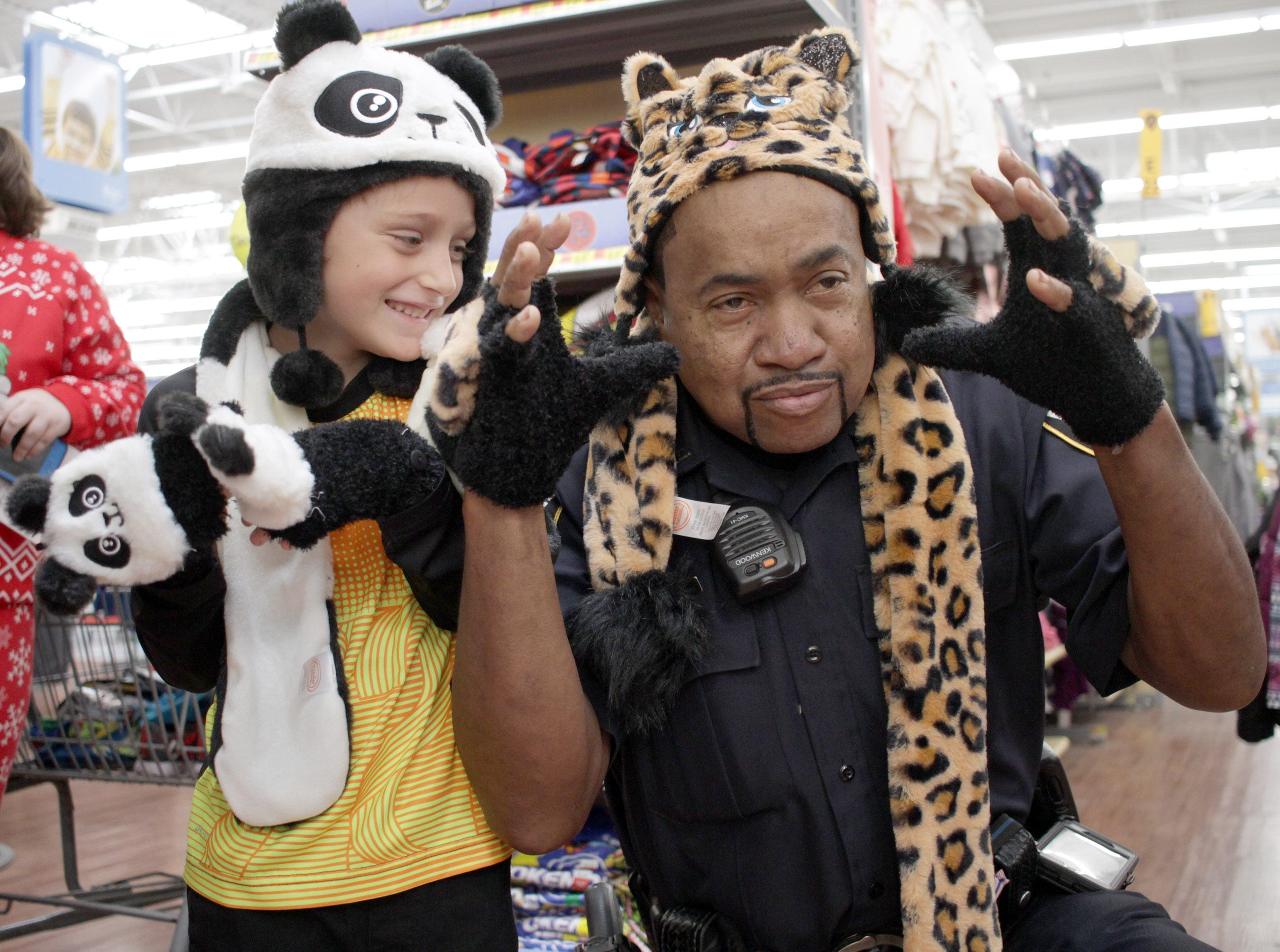 Richard Allens is amused at Officer JT Smith's impersonation of CATS during Shop with a Cop in Ashland City on Saturday, December 15, 2018.