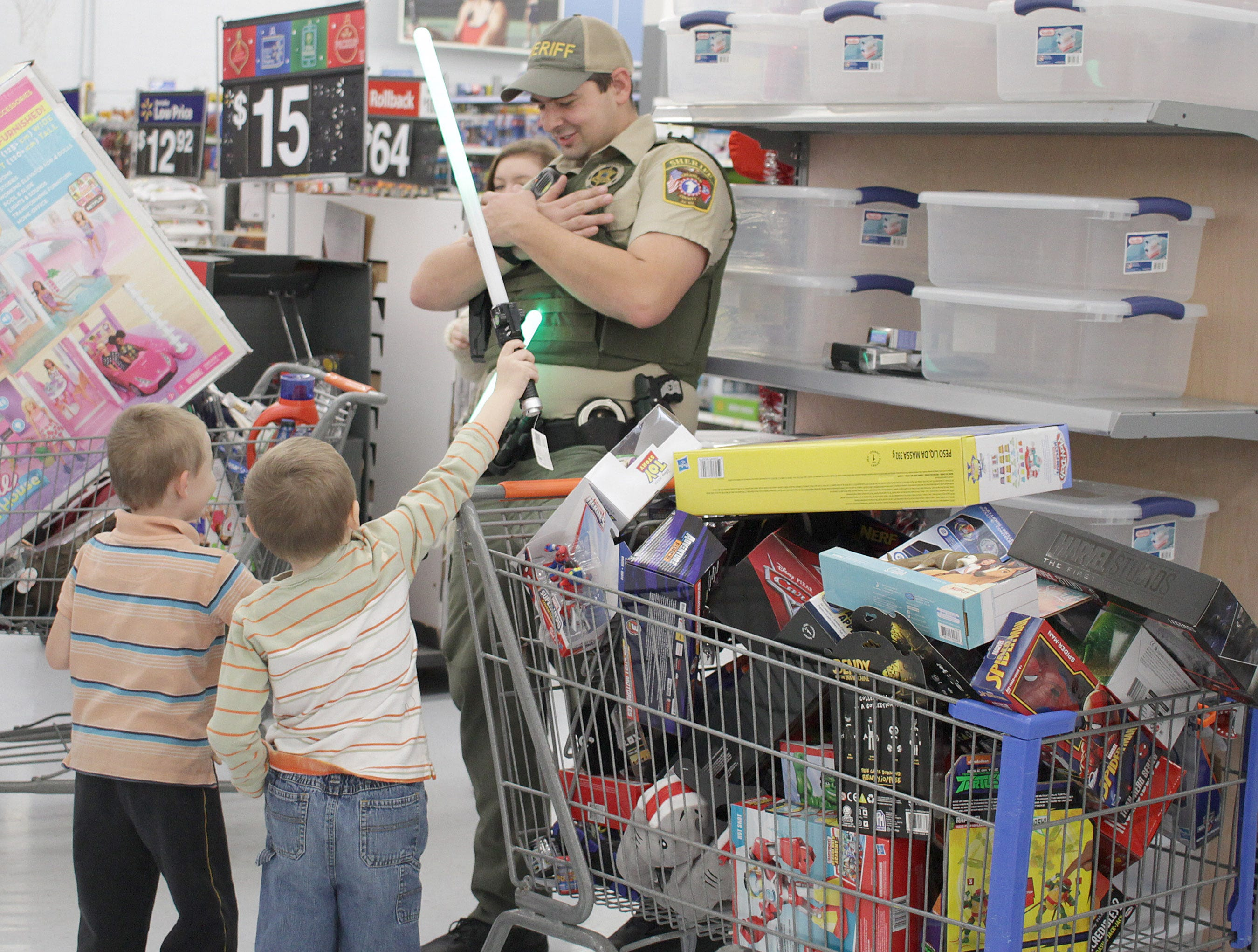 Twins Travis and Steven Jones attack Officer Brandon Scruggs with light sabers during Shop with a Cop in Ashland City on Saturday, December 15, 2018.