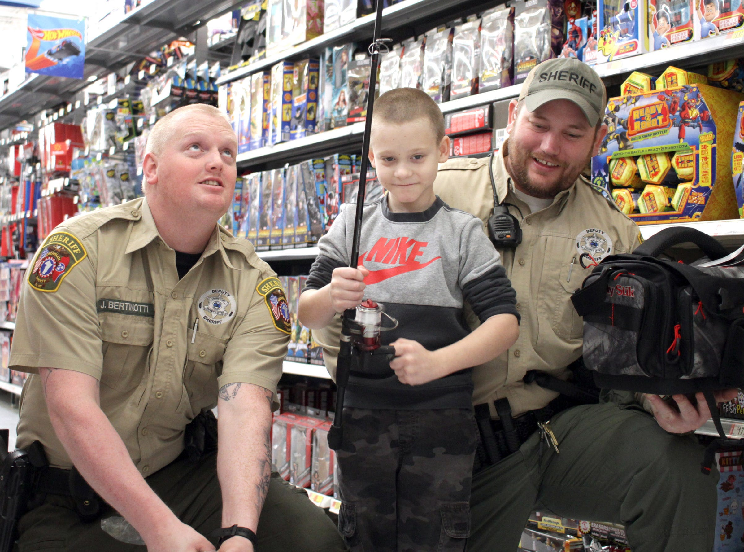 Tyler Allen (8) shops for fishing equipment with Officer James Bertinotti and Travis Kretz at Shop with a Cop in Ashland City on Saturday, December 15, 2018.