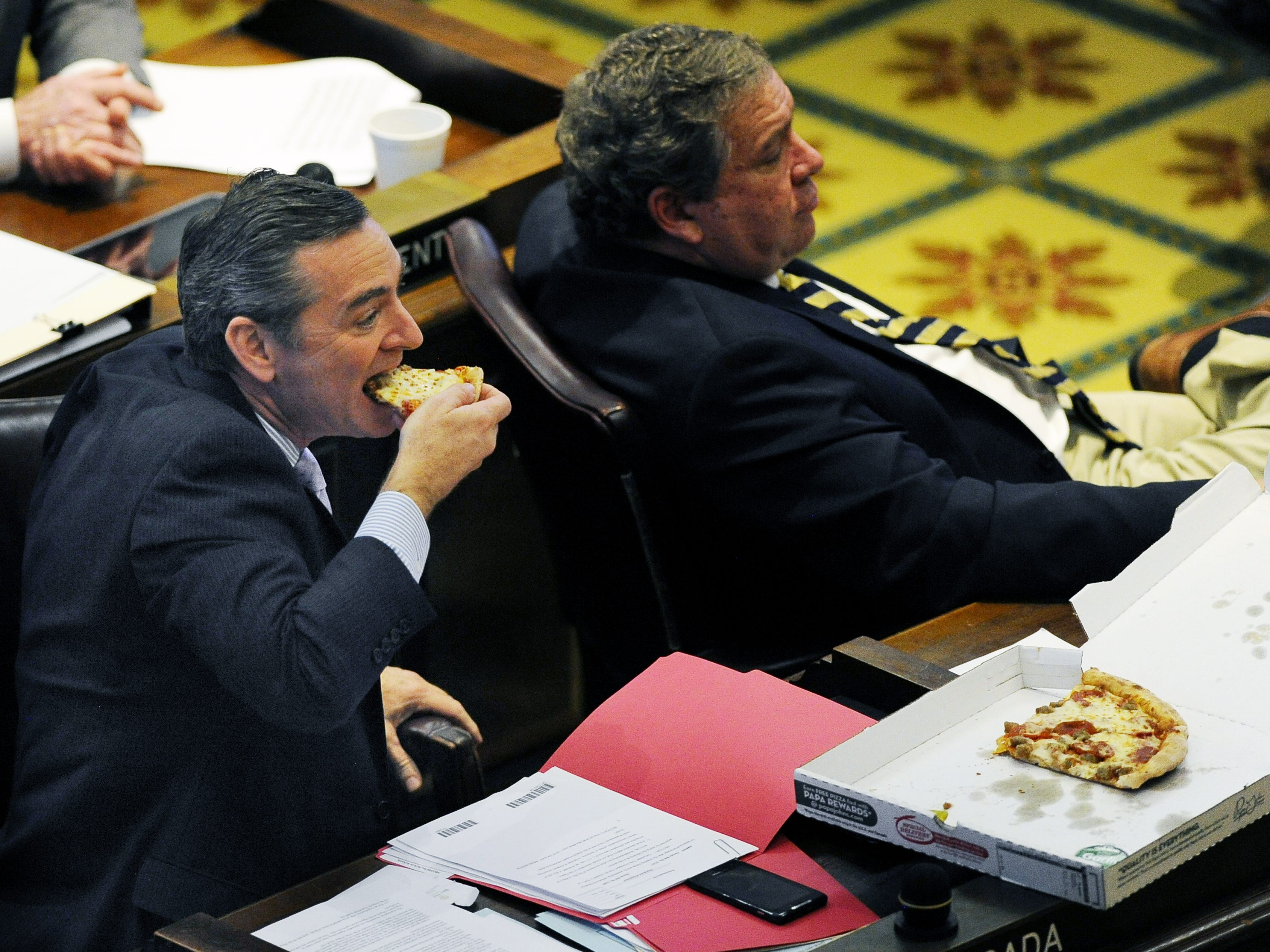 Rep. Glen Casada, left, eats pizza during a House of Representatives session at the Capitol on March 13, 2014.