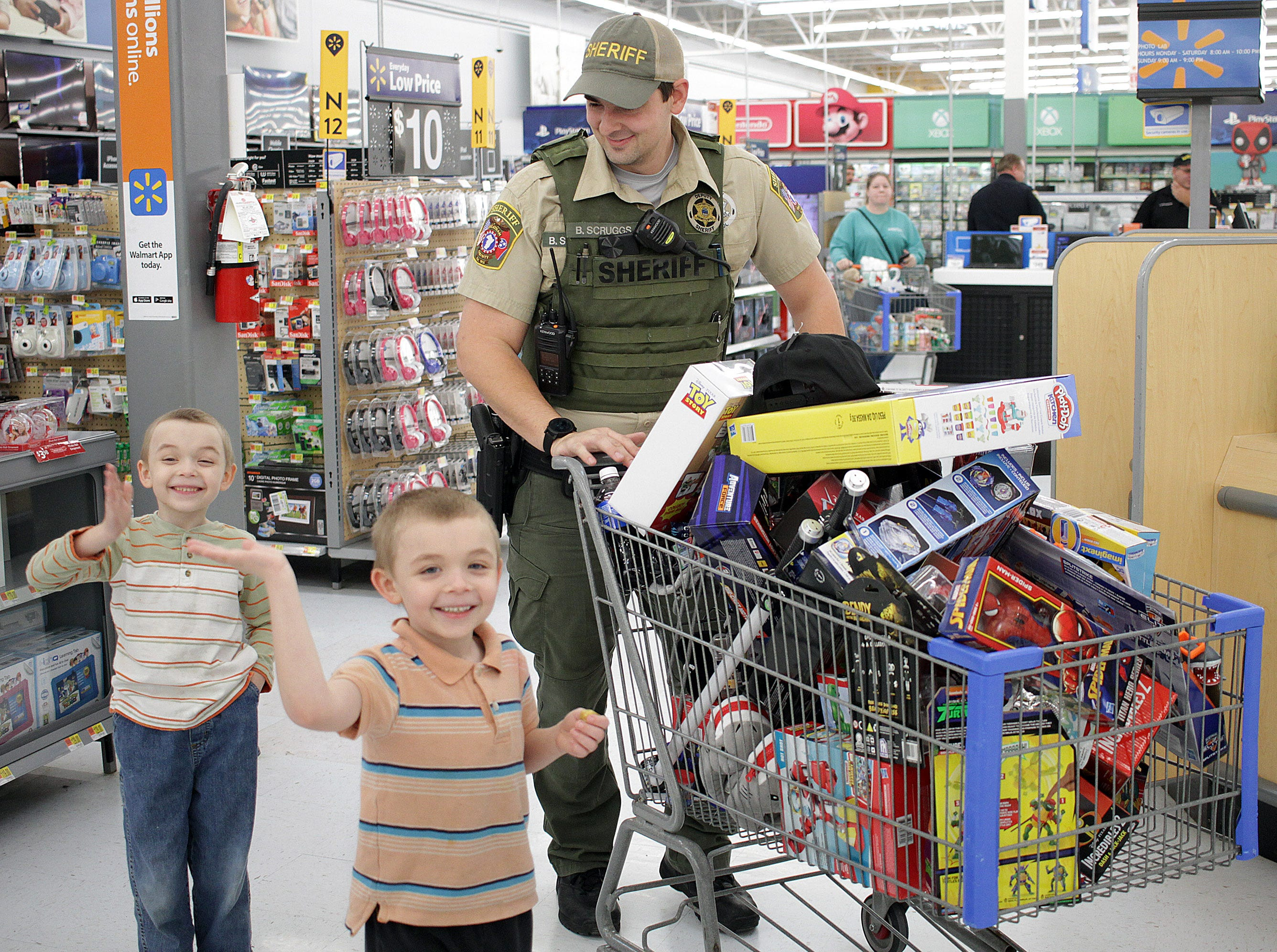 Twins Travis and Steven Jones (6)  shop with Officer Brandon Scruggs at Shop with a Cop in Ashland City on Saturday, December 15, 2018.