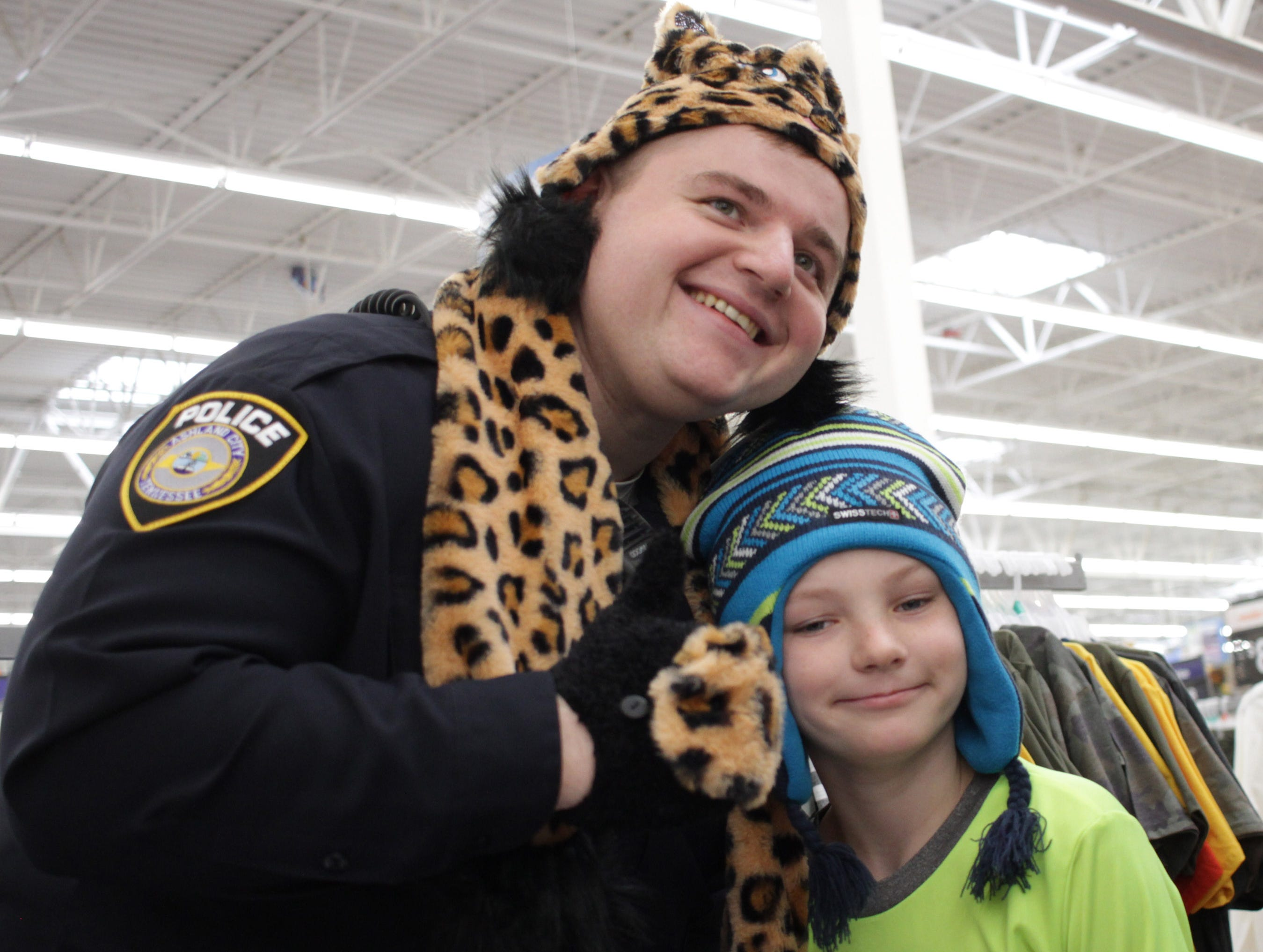 Officer Paul Garrett and Dalton Weaver (9) try on hats during Shop with a Cop in Ashland City on Saturday, December 15, 2018.