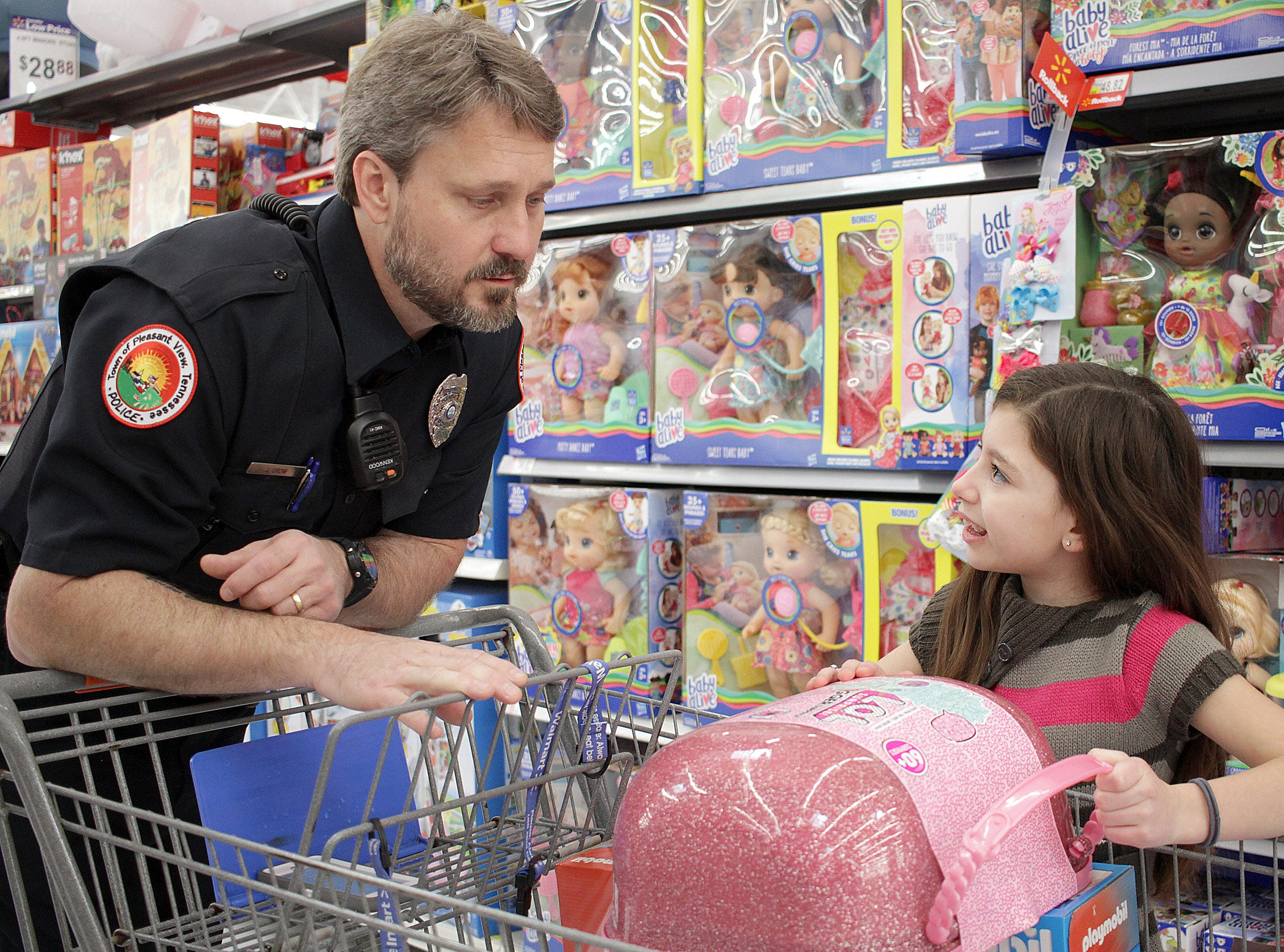 Officer Jeff Crow and Jazmyne McCoy discuss purchase options during Shop with a Cop in Ashland City on Saturday, December 15, 2018.