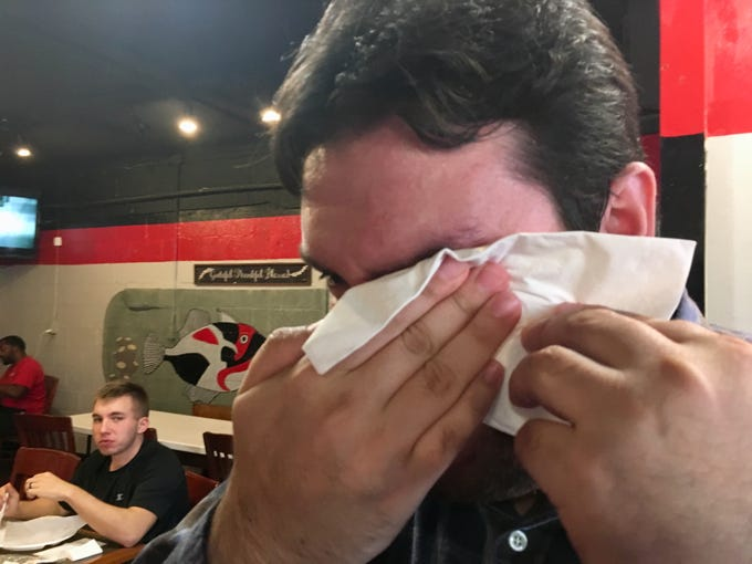 When the sweat mingles with the tears: Tennessean hot chicken taster Juan Buitrago wipes his eyes after eating Bolton's hot chicken