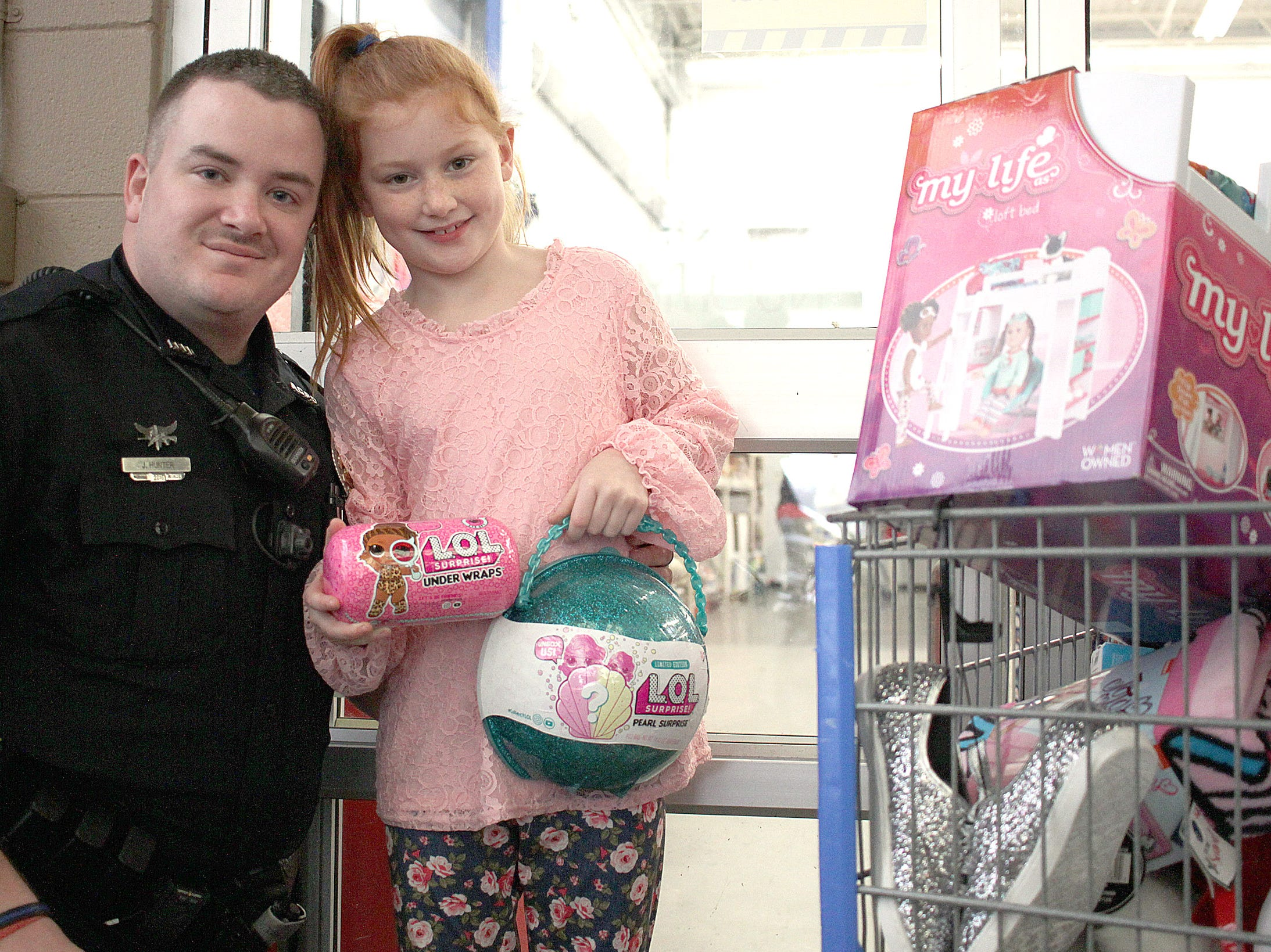 Officer Nick Hunter and Abigail Byrd have some LOL dolls as they get in line at Shop with a Cop in Ashland City on Saturday, December 15, 2018.