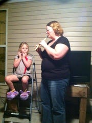 Julie Nidiffer, right, around Christmas 2016, just before she lost 90 pounds playing pickeball. Nidiffer is playing a recorder with her then 8-year-old great niece, Mya Jane Rockensock at her niece's house in Wilson County.