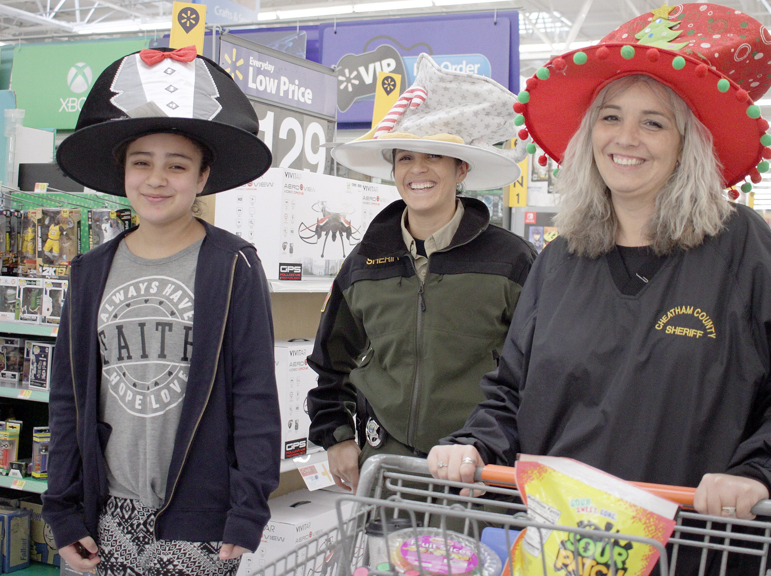 L-R Carley Penaloze, Deputy Dahianna Arguello and Amy Harris wear silly hats during Shop with a Cop in Ashland City, TN on Saturday, December 15, 2018.