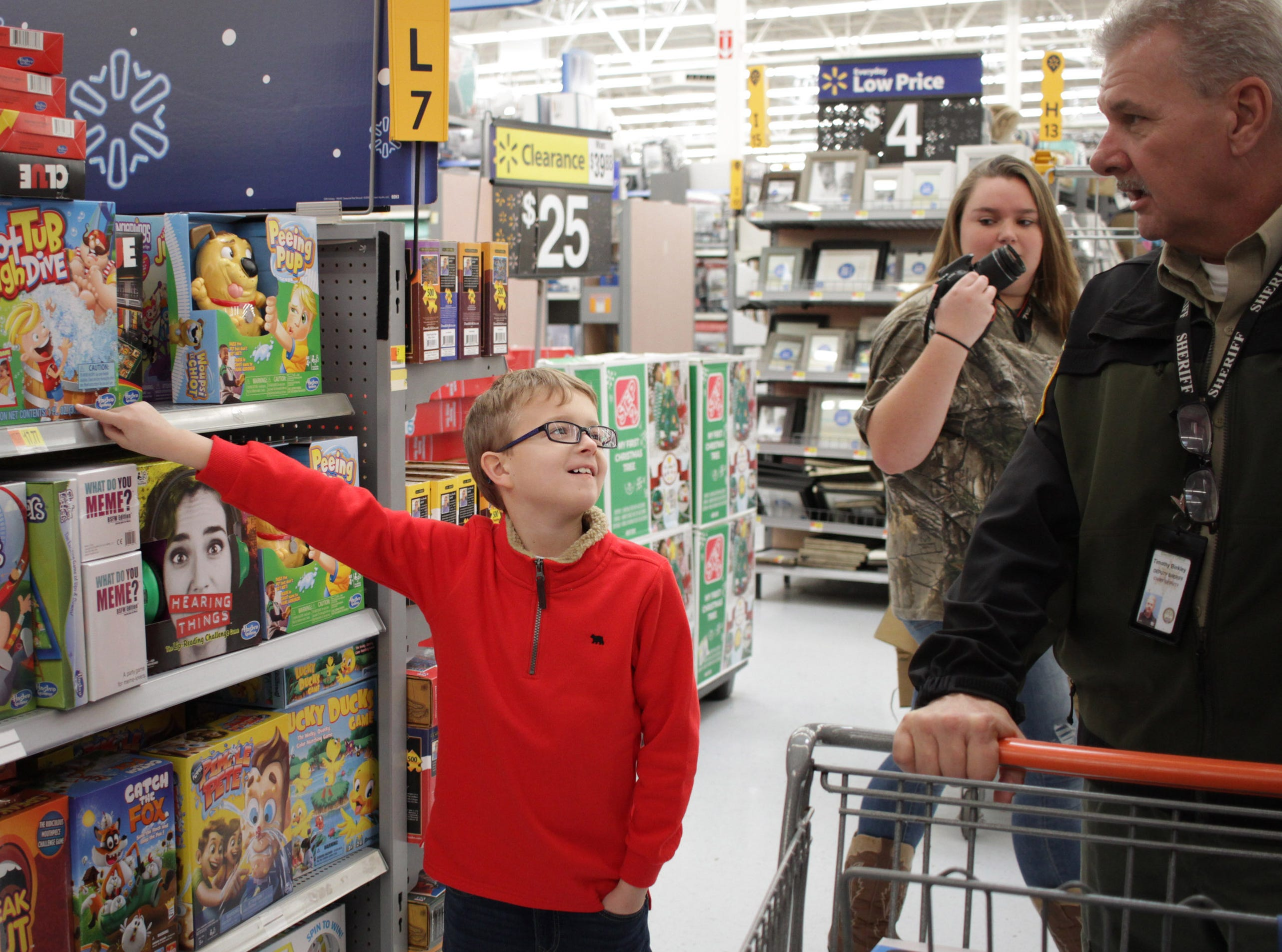 Peyton Whitt (9) points the the Hot Tib High Dive game as he shop with Officer Tim Binkley in Ashland City on Saturday, December 15, 2018.