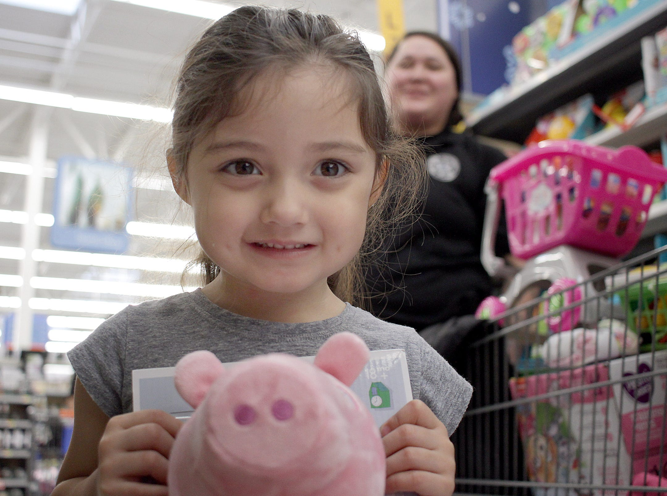 Marianna Penaloza (2) picks out a Piggy Doll with Deputy Rashia Biggs at Shop with a Cop in Ashland City on Saturday, December 15, 2018.