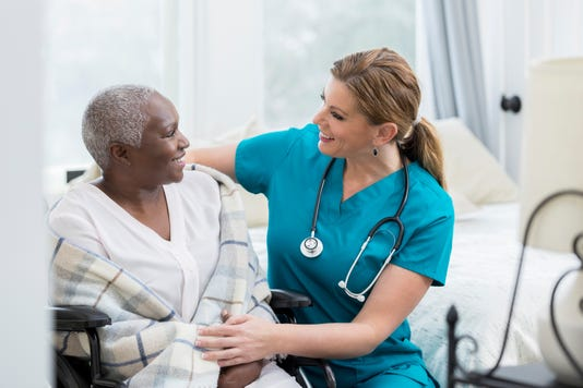 Caring Nurse Talks With Senior Female Patient