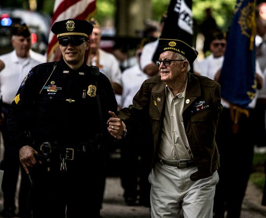 Local veteran and retired Denison University professor Andrew Sterrett is escorted to his seat for the 150th Granville Memorial Day celebration.