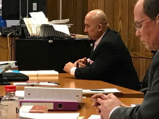 Assistant Prosecutor Jorge Morales looks glum moments after the verdict was read acquitting three defendants of murder. In the foreground is defense attorney Paul Condon.
