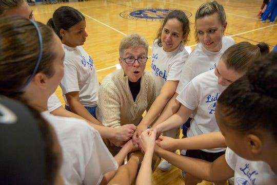Longtime girls basketball coach Sue Liddy gets her  team players started before they headed out to the court. The game and court floor were dedicated to her today during the  Academy of the Holy Angels gym dedication ceremony on Dec. 16, 2018  in Demarest, NJ.