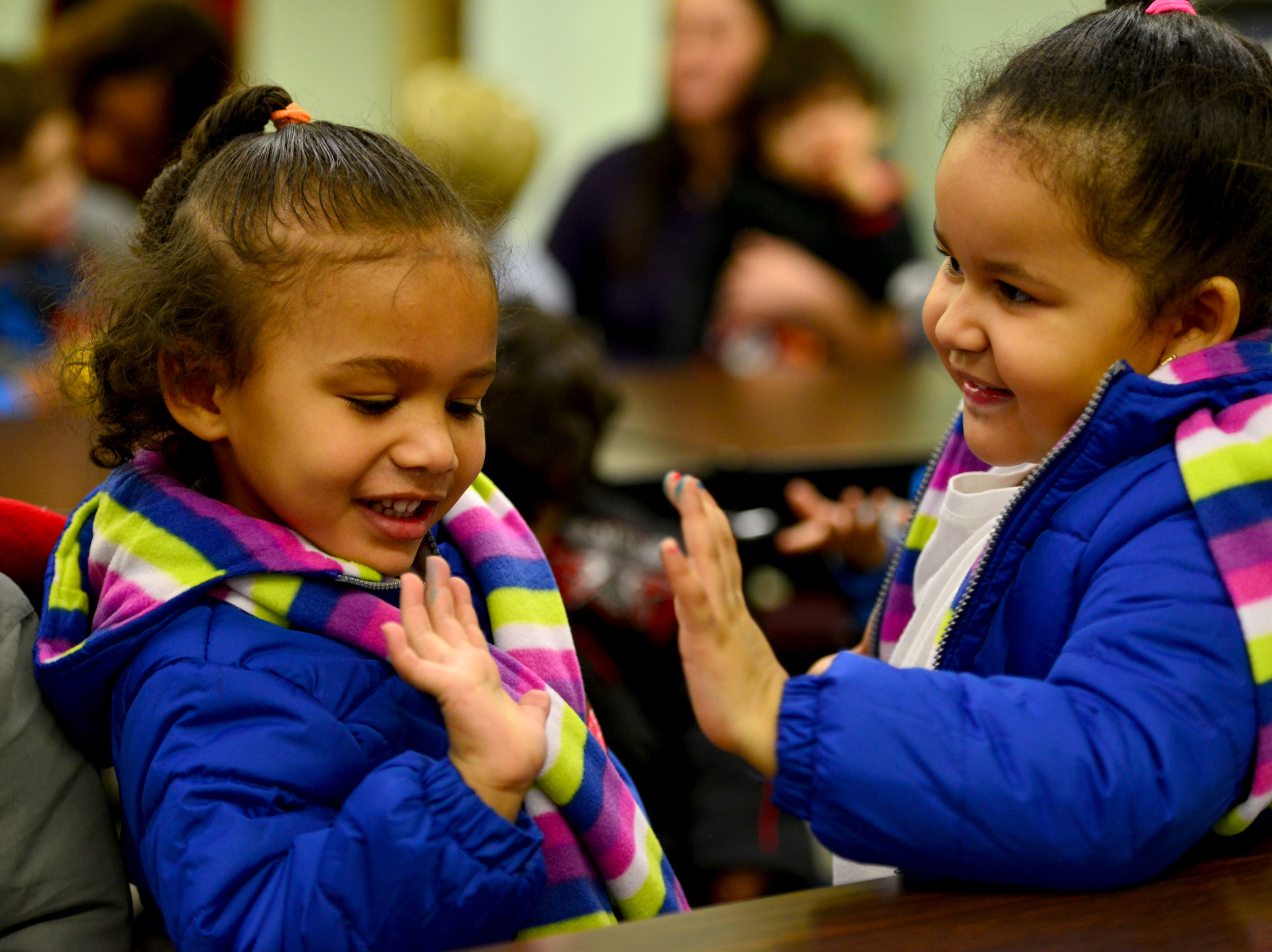 From left, Hailey Davis and Milani Nieves, PreK3 students, give each other a high five after putting on their new coats. The Paterson Rotary held their eighth annual Christmas Coat Drive in Paterson, on Monday morning December 17, 2018. The club donated coats to all the students at Edward W. Kilpatrick Elementary School. The Rotary Club raised funds from its members and the community to buy 380 coats for the students.