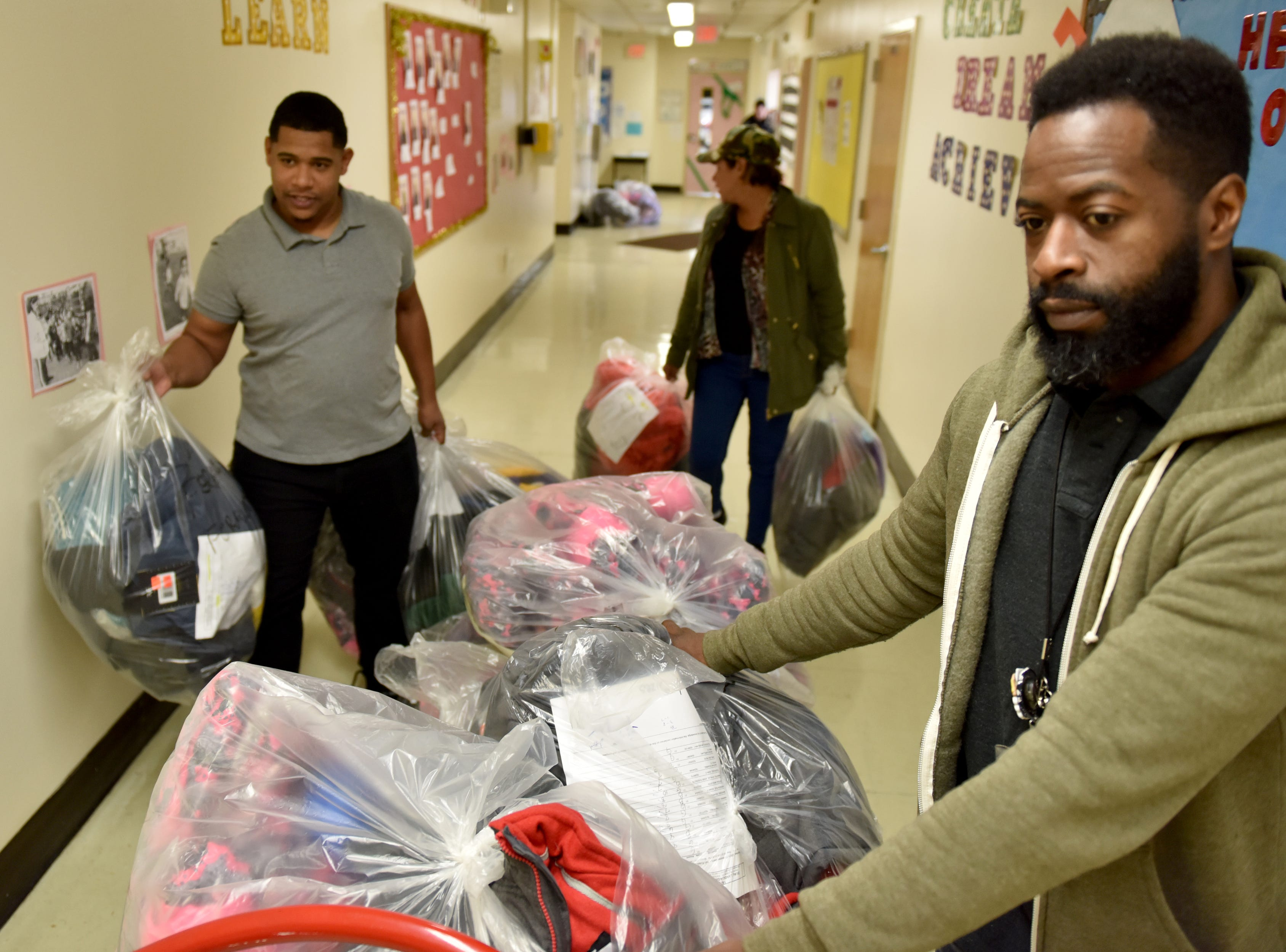 Jarrod Rogers, Jonathan Cruz and Marlene Garcia move the bags of new coats through the school. The Paterson Rotary held their eighth annual Christmas Coat Drive in Paterson, on Monday morning December 17, 2018. The club donated coats to all the students at Edward W. Kilpatrick Elementary School. The Rotary Club raised funds from its members and the community to buy 380 coats for the students.