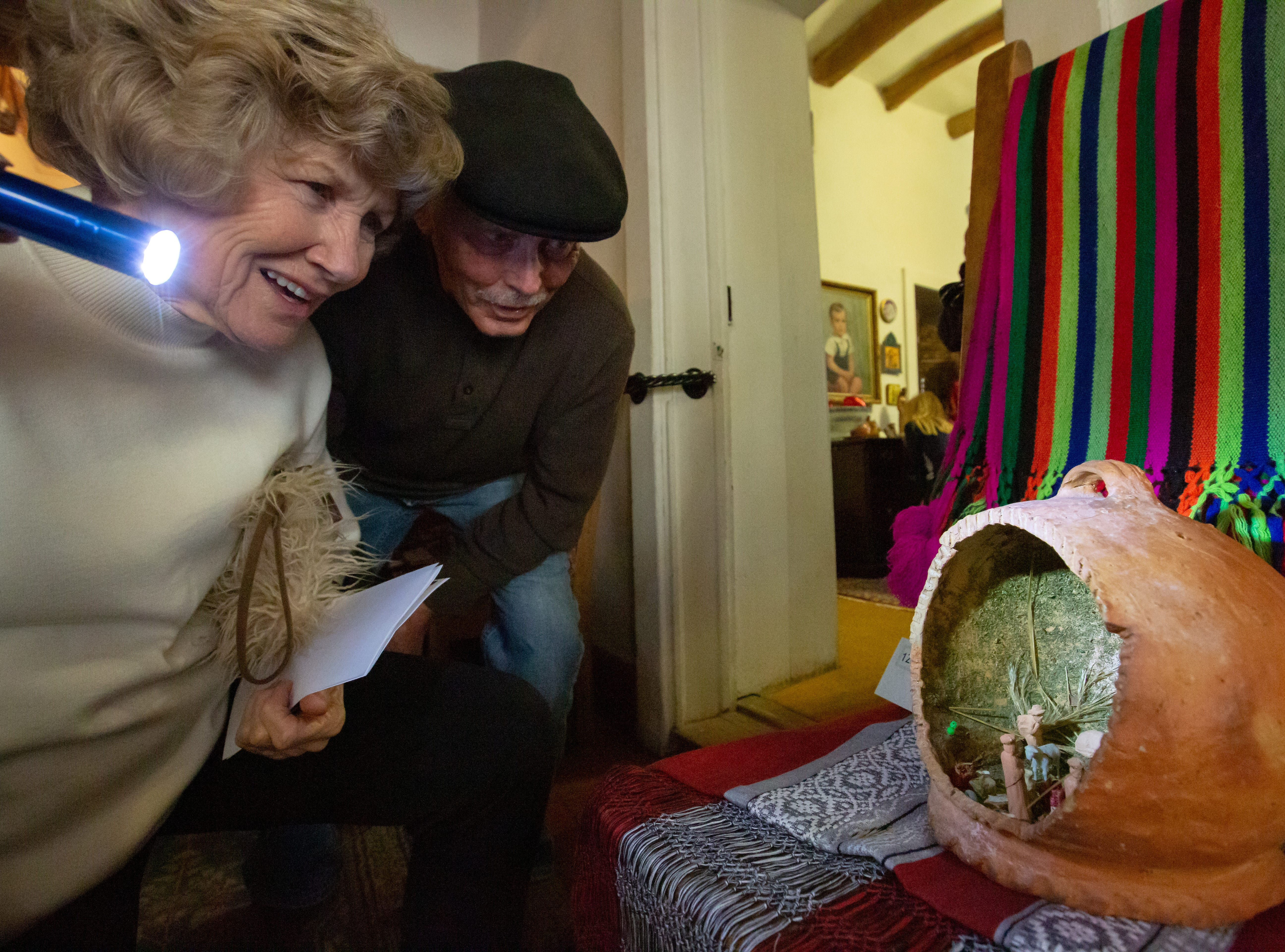 Pat Green, left, and Ernst Volleter look at nativity scenes on Sunday, December 16, 2018, during Nacimiento Open House with J. Paul Taylor at the Taylor-Barela-Reynolds-Mesilla Historic Site located in the Mesilla Plaza.