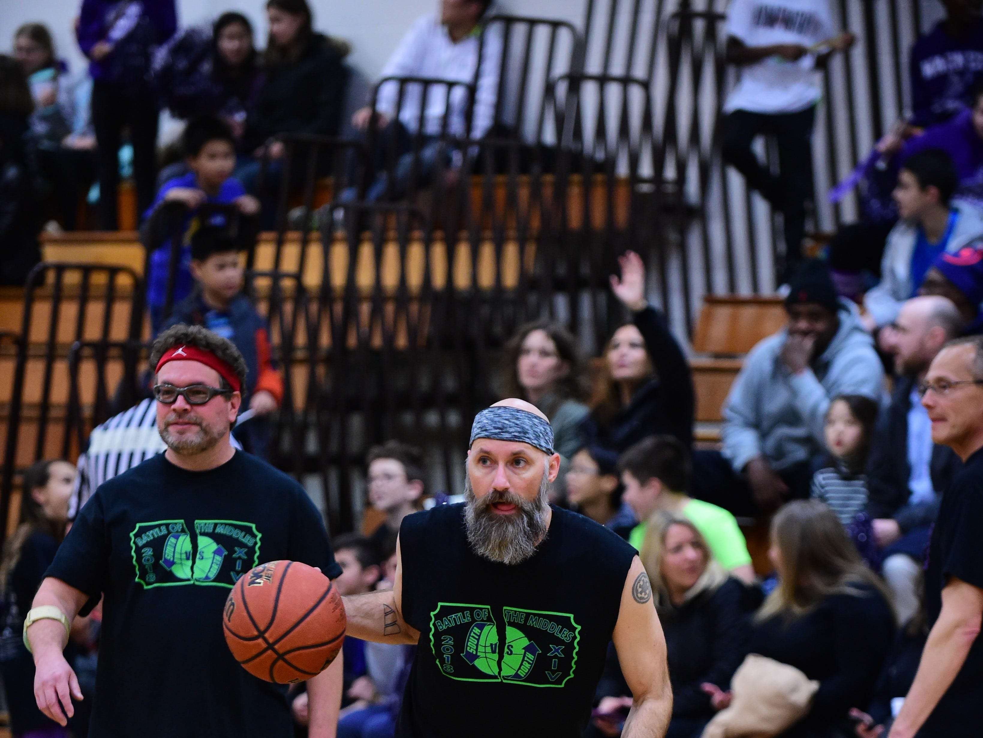 Teachers warm up prior to the Battle of the Middles staff charity basketball game held Friday evening at Harrison.