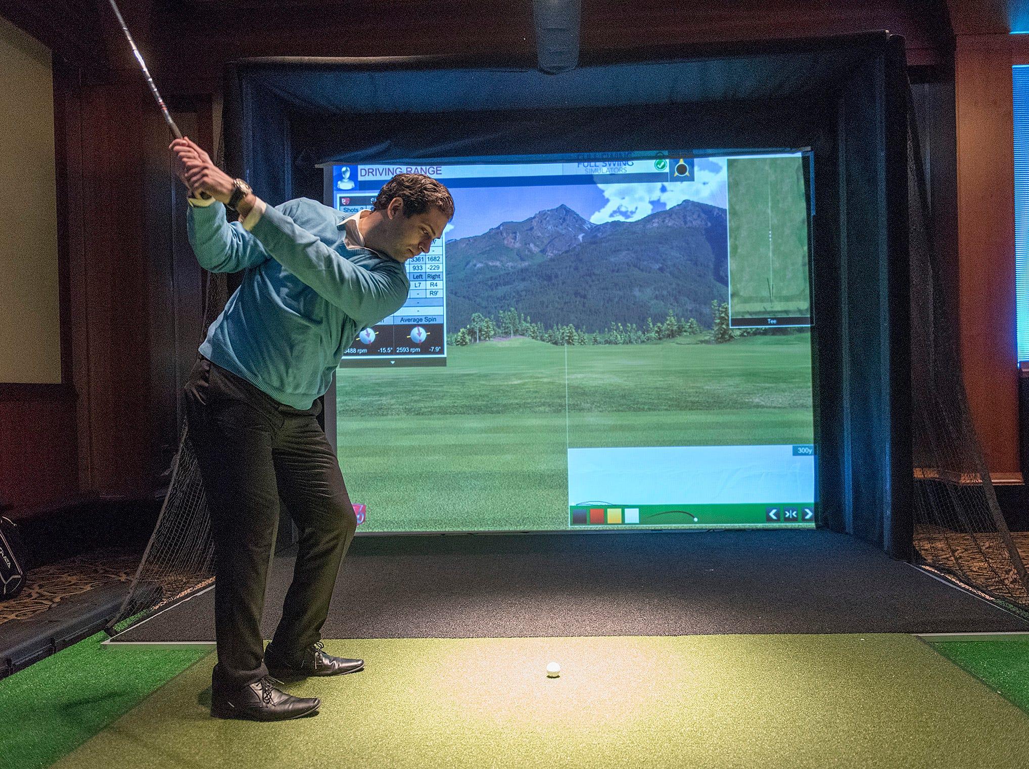 Sam Mass takes a swing at the golf simulator.