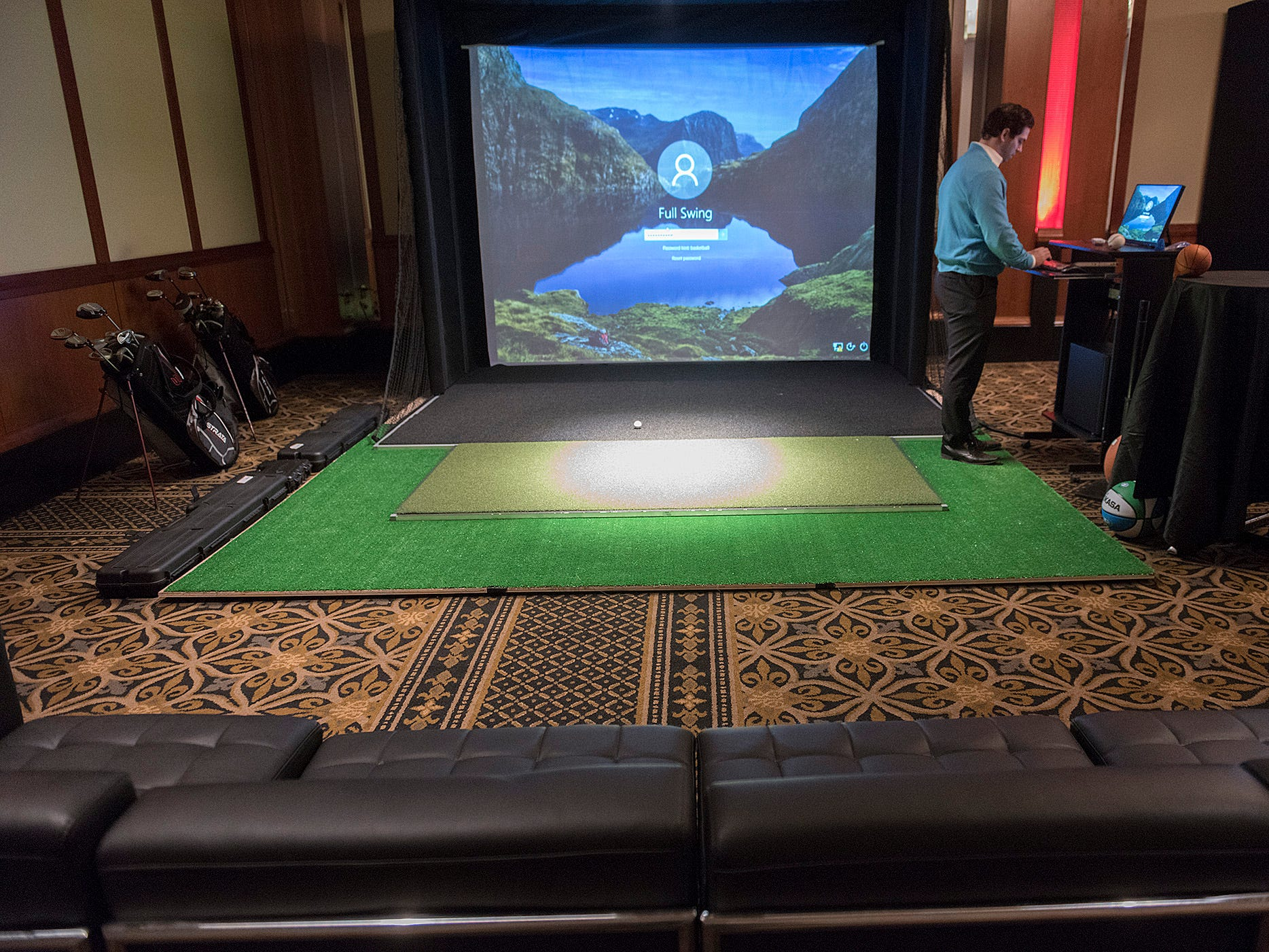 Sam Mass sets up a game. Each screen area has comfortable seating, seen in the foreground.