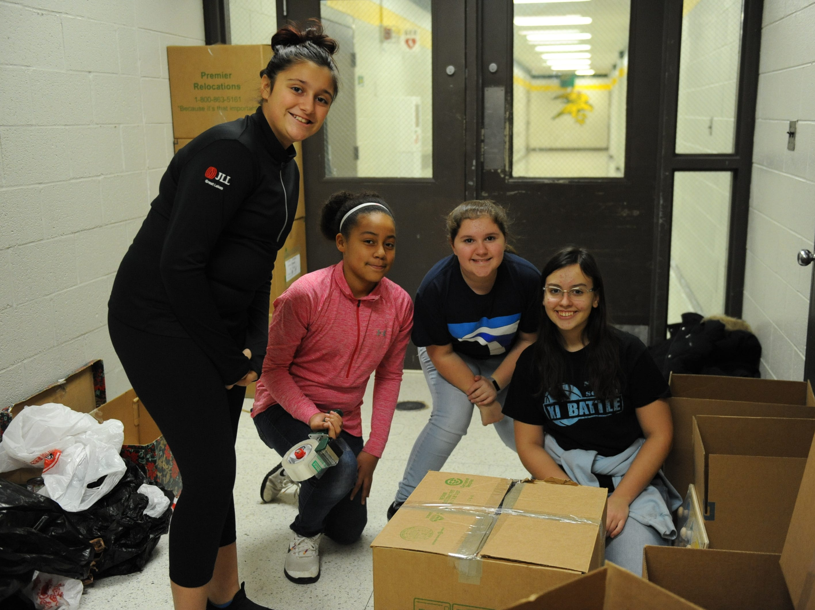 Power Middle School students Soseh Broglin, Edimari King, Abigail Brooke and Gabriella Camaj pack items that were brought to the annual charity game Friday evening.