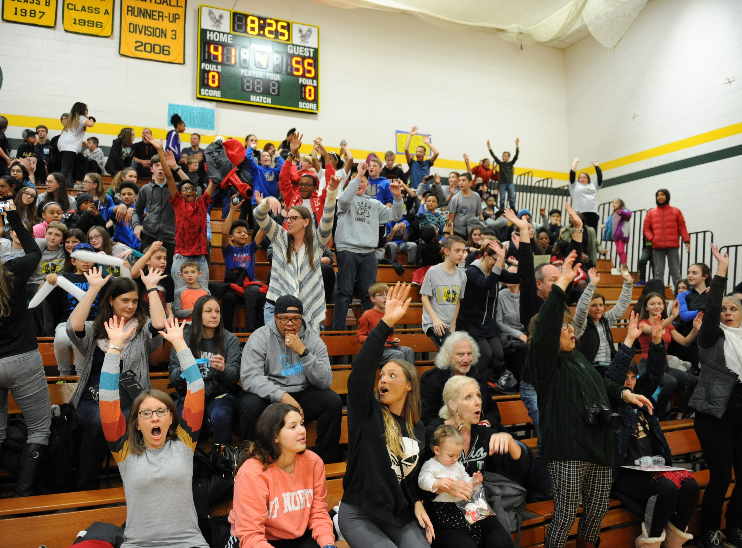 "The ""Wave"" makes its way around the gym during the battle of the middles game."