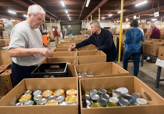 Charlie Davis and Scott Daniels volunteer to sort canned food items at Manna Food Pantry on Monday. The organization has officially dedicated its Bear Family Foundation Center for Hope.