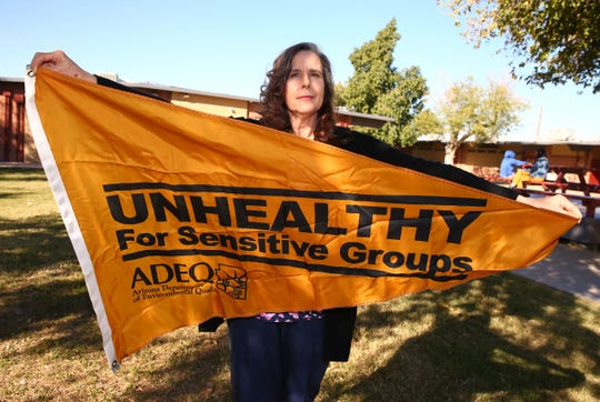 Irene Lopez Elementary School nurse Lois Leon holds the orange flag that warns of unhealthy air pollution that could affect people with respiratory problems.
