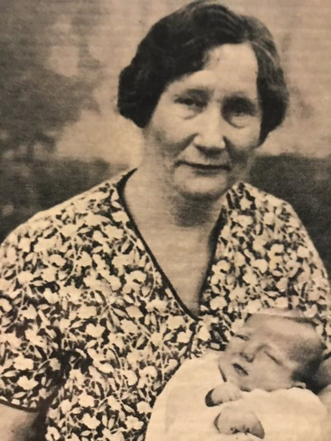 Helen Dana, the midwife who cared for the Hatbox Baby after she was discovered, pictured holding Sharon Elliott in 1931.
