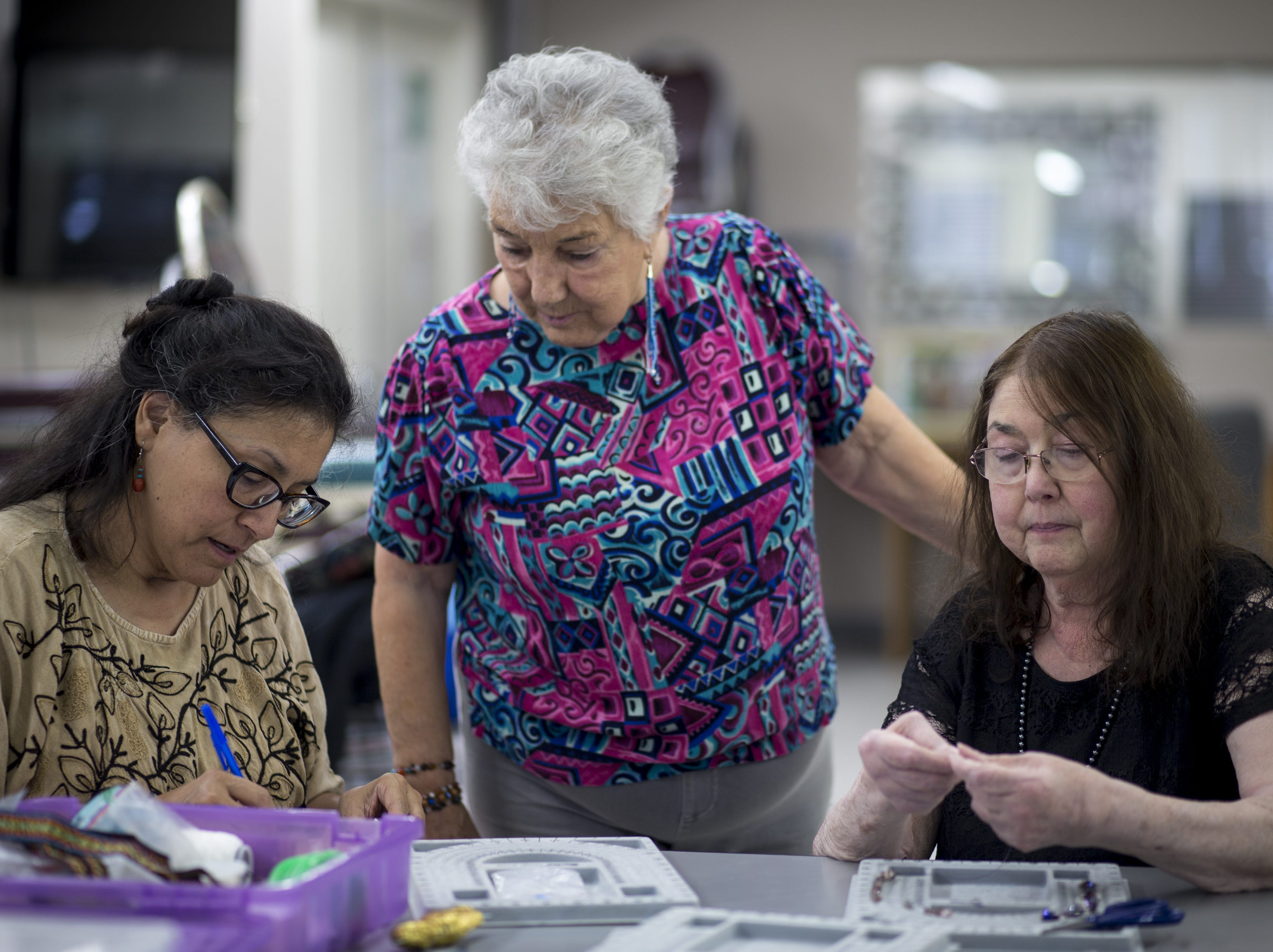 Barbara Cory (right) and Cynthia Fodness make jewelry, Dec. 12, 2018 at Phoenix Senior Opportunities, 1220 S. Seventh Ave. in Phoenix. Looking on is their instructor, Fina Gaffney (center). Cory copes with asthma that can flare up when smog worsens in Phoenix's winter months.