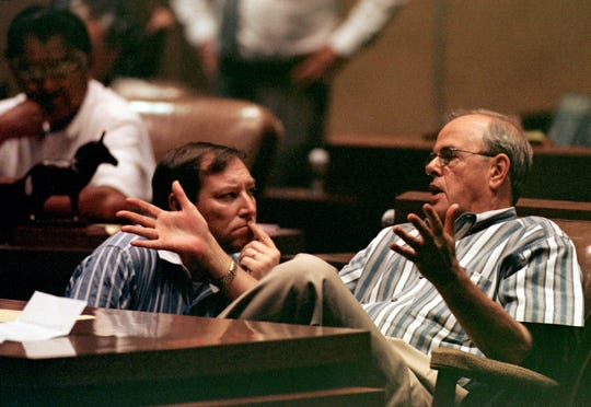 Arizona State Sen. John Wettaw, R-Flagstaff, (right) confers with Sen. Darden Hamilton, R-Glendale, (center) as Sen. Jack Jackson, D-Window Rock (left) listens in during a vote on Gov. Jane Hull's controversial school funding plan June 28, 2000, at the State Capitol in Phoenix.