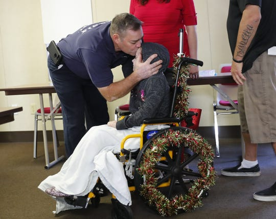 Isabella McCune gets a kiss from Phoenix Firefighter David Ford after being reunited at the Arizona Burn Center in Phoenix on Dec. 17, 2018. Ford was one of the first responders that helped her after she was severely burned in March. The 9-year-old was  discharged nine months to the day after her accident.