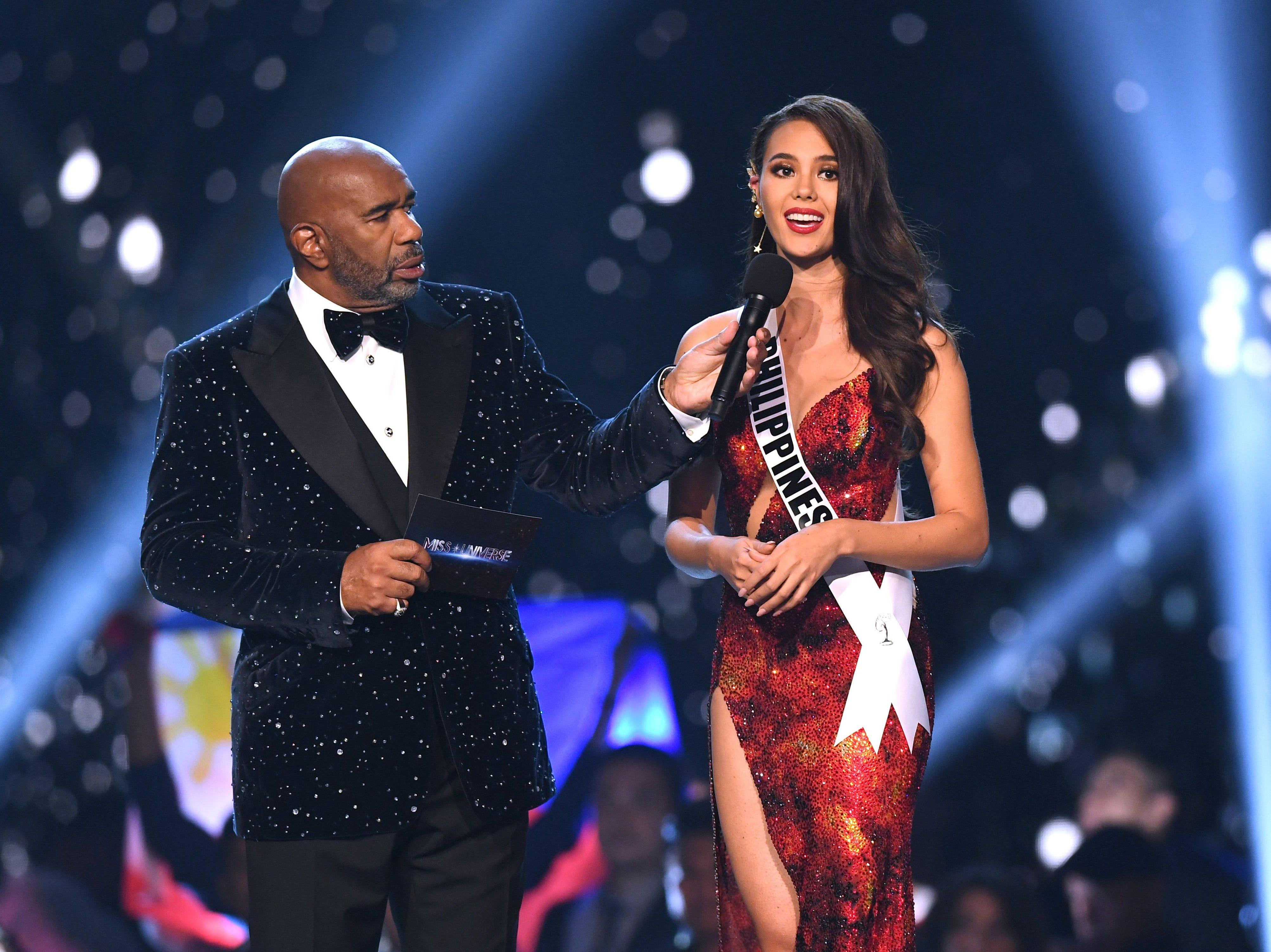 Catriona Gray (der) de Filipinas habla mientras el anfitrión Steve Harvey escuchadurante  la ronda final a los tres finalistas del concurso Miss Universo 2018 en Bangkok el 17 de diciembre de 2018.