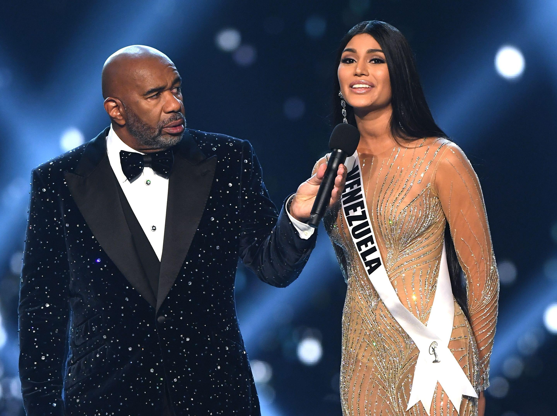 Sthefany Gutiérrez (der) de Venezuela habla mientras el anfitrión Steve Harvey escucha en la ronda final a los tres finalistas del concurso Miss Universo 2018 en Bangkok el 17 de diciembre de 2018.