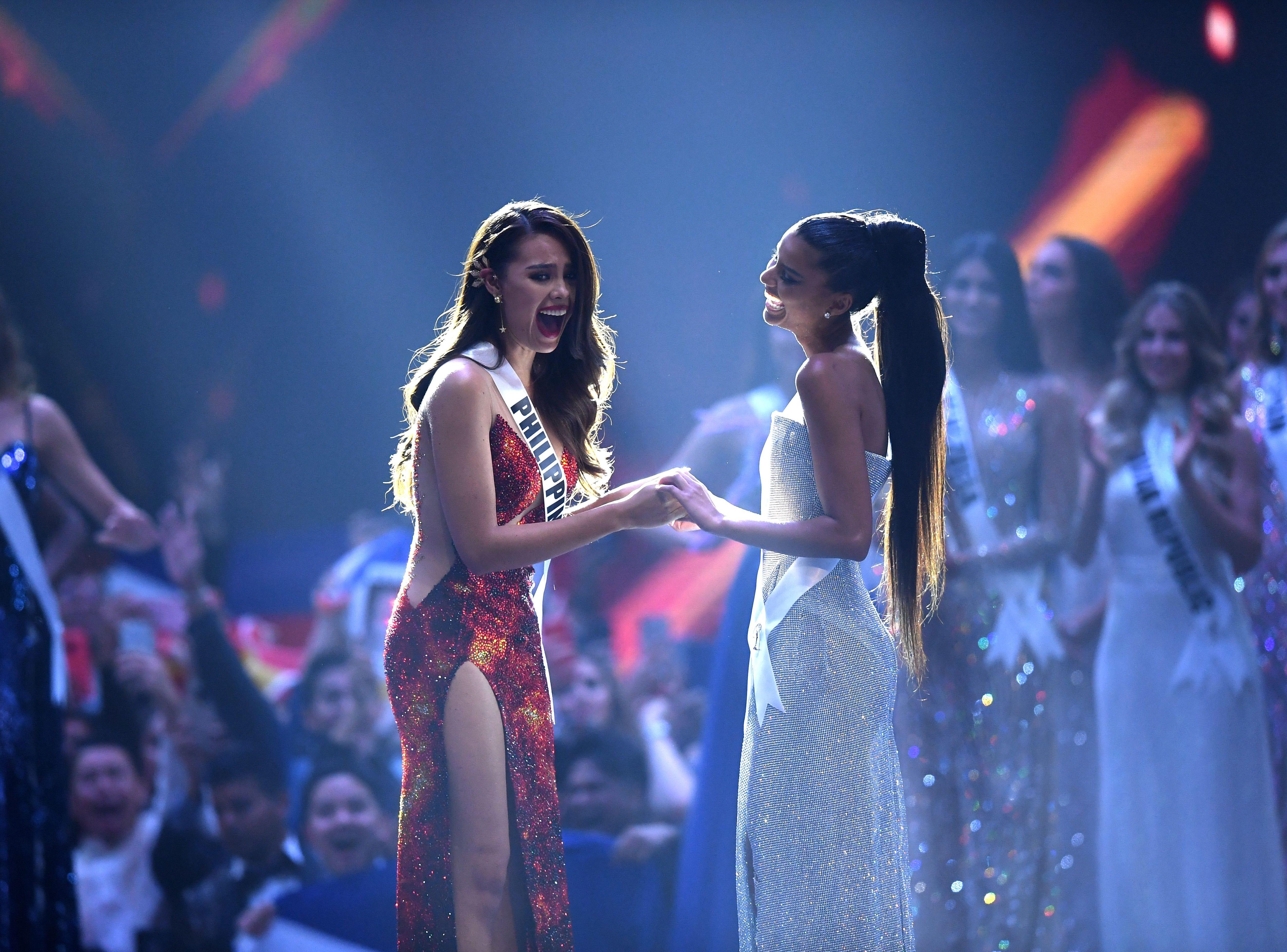 Catriona Gray de Filipinas (izq) reacciona al saberse ganadora de Miss Universo 2018 con la segunda finalista de Miss Universo Tamaryn Green de Sudáfrica el 17 de diciembre de 2018 en Bangkok.