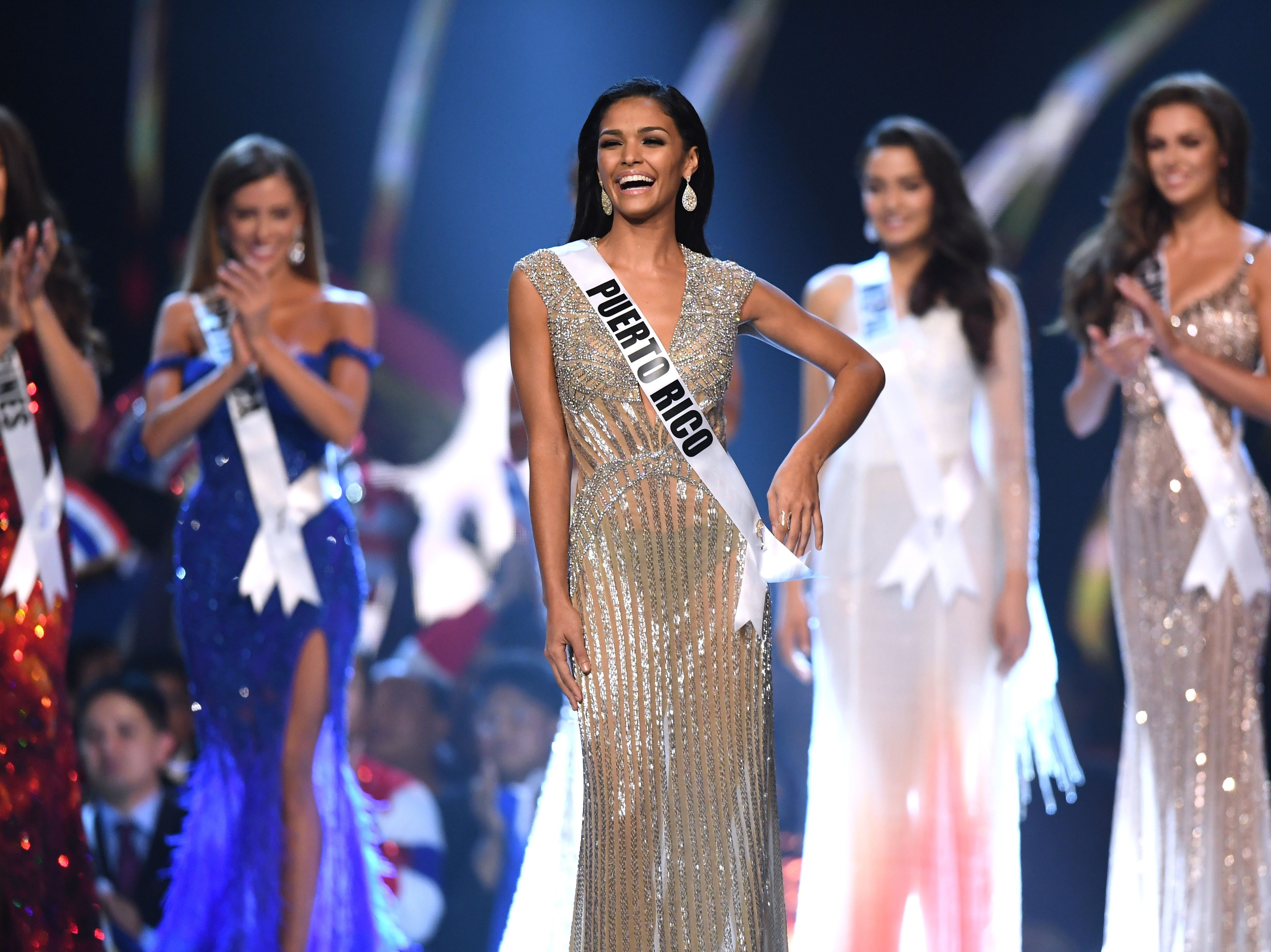 Kiara Ortega (centro) de Puerto Rico reacciona después de haber sido seleccionado entre los cinco primeros finalistas en el concurso Miss Universo de 2018 en Bangkok el 17 de diciembre de 2018.