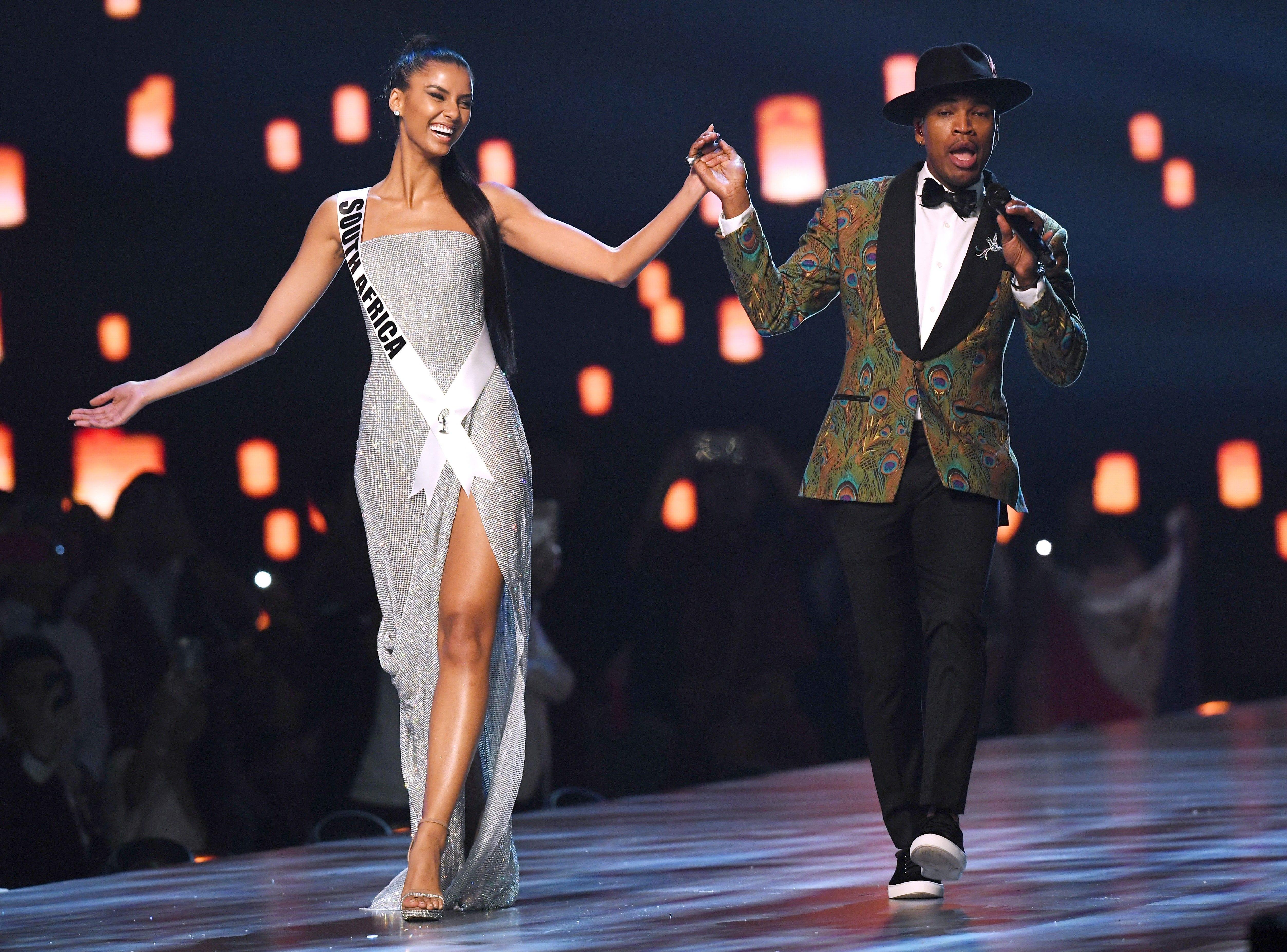 Tamaryn Green (izq) de Sudáfrica toma la mano mientras el artista estadounidense Ne-Yo se presenta en el escenario durante el concurso Miss Universo 2018 en Bangkok el 17 de diciembre de 2018.