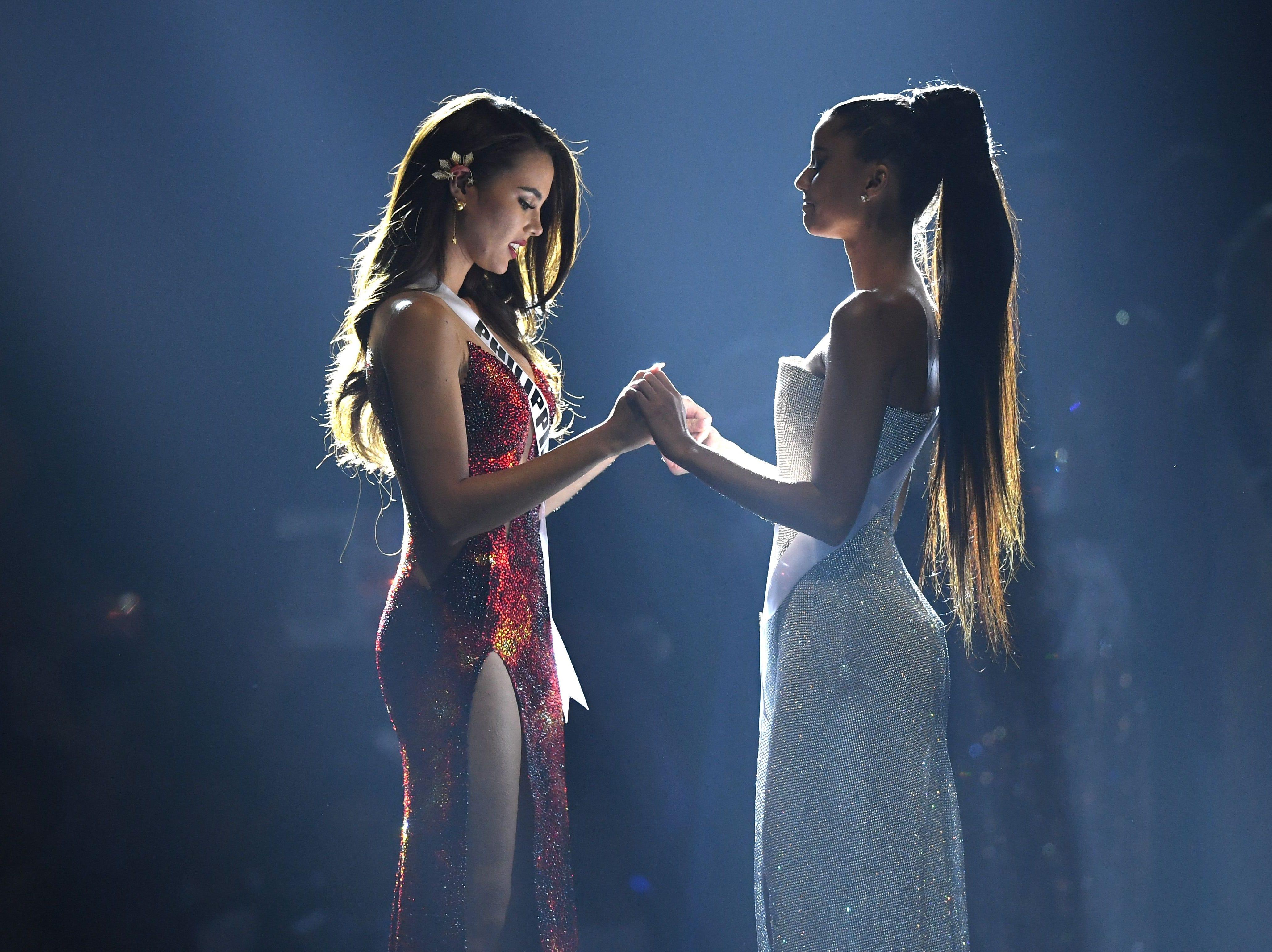 Las dos finalistas principales, Catriona Grey de Filipinas (izq) y Tamaryn Green de Sudáfrica, se dan la mano mientras esperan el anuncio de la ganadora durante el concurso Miss Universo 2018 en Bangkok el 17 de diciembre de 2018.
