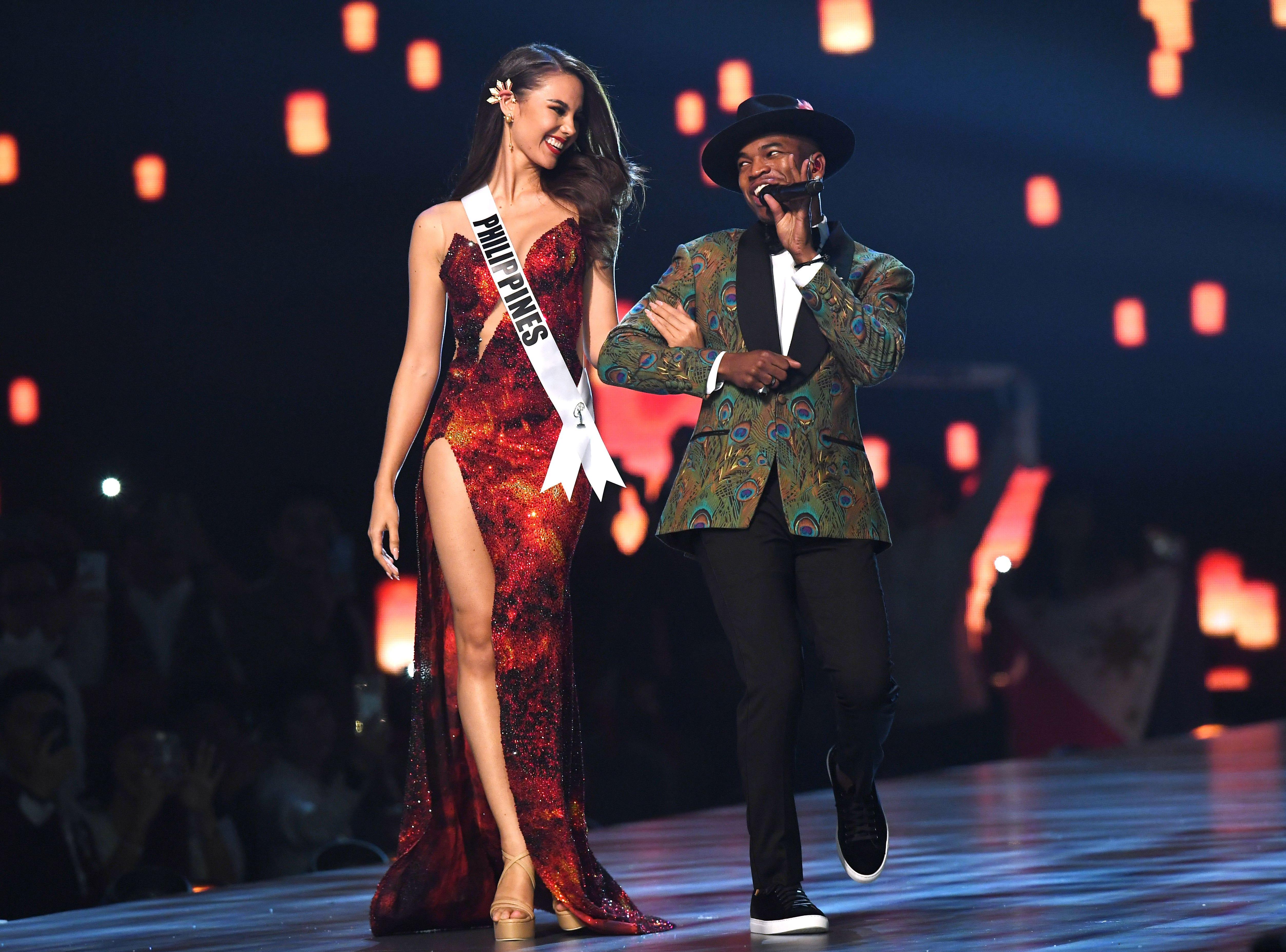 Catriona Gray (izq) de Filipinas mira mientras el artista estadounidense Ne-Yo se presenta en el escenario durante el concurso Miss Universo 2018 en Bangkok el 17 de diciembre de 2018.