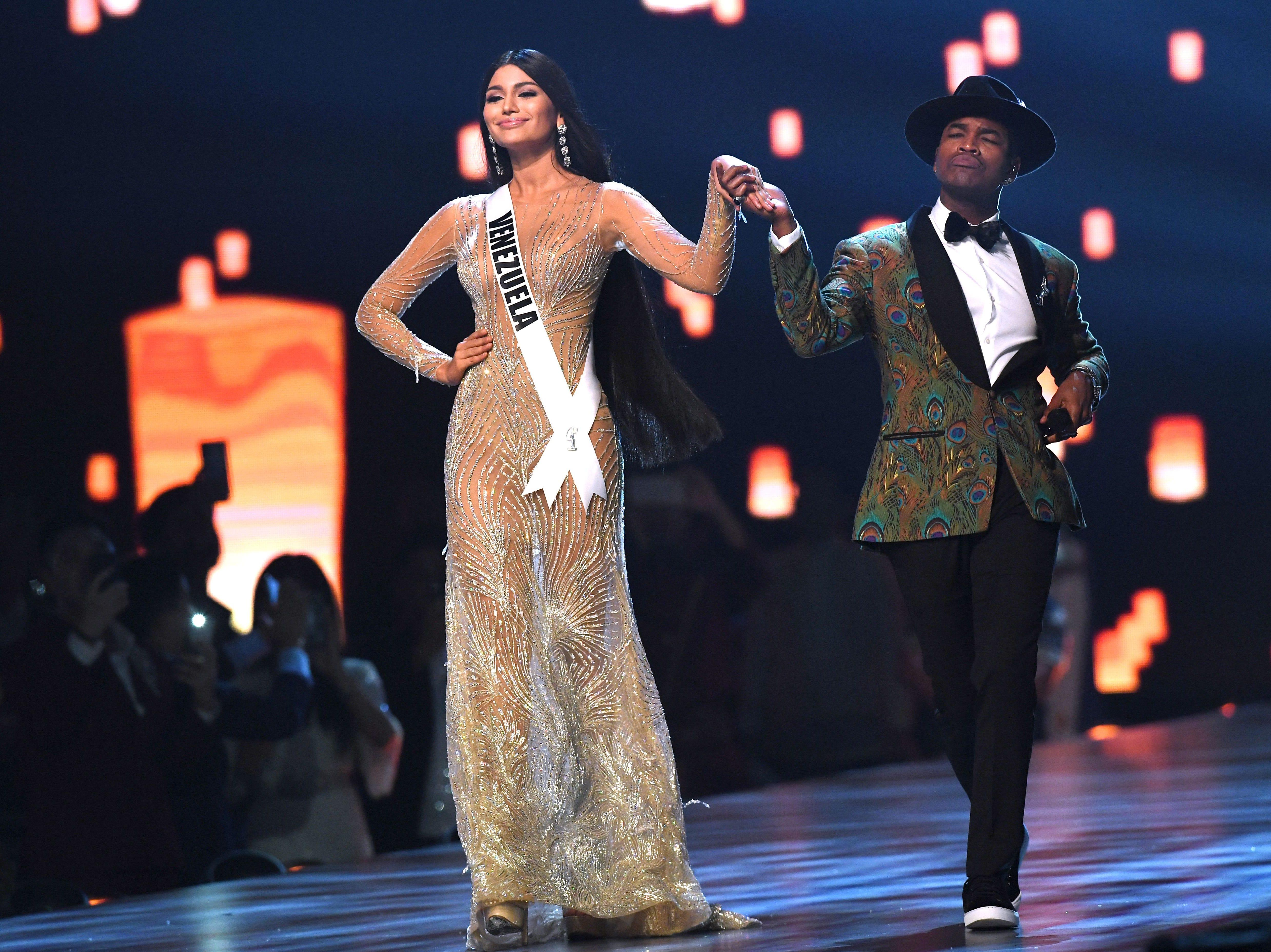 Sthefany Gutiérrez (izq) de Venezuela se toma de la mano mientras el artista estadounidense Ne-Yo se presenta en el escenario durante el concurso Miss Universo 2018 en Bangkok el 17 de diciembre de 2018.