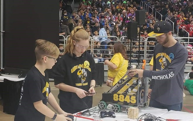 Memphis Wild Bees drive team Ellie and Mason Milles work on the team's robot along with Drive team coach Nick Haack.