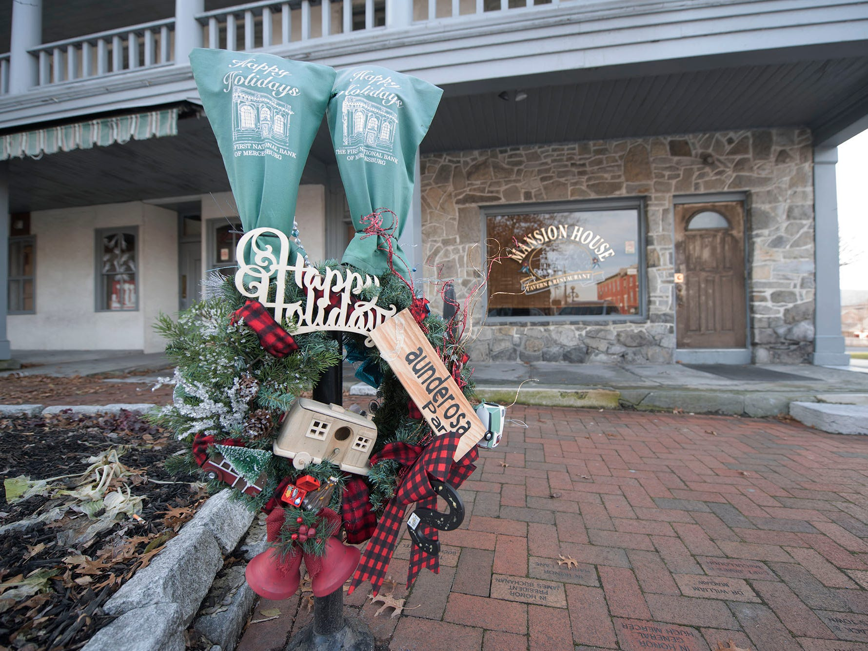 Parking meters in Downtown Mercersburg are decorated with Christmas wreaths and holiday messages.