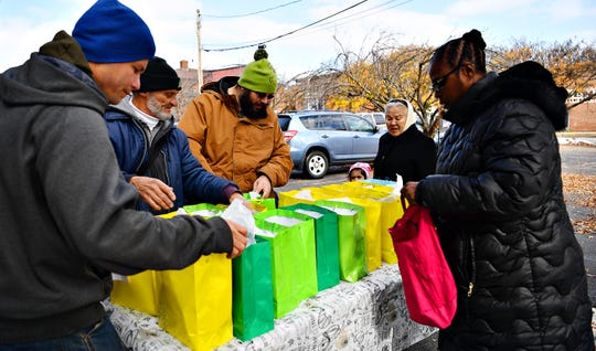 Lorraine Eady-Simpson, right, of Turning Point Transitional Services, Inc., hands out bags to homeless, adult males alongside York Giving Helping Hands as volunteers serve a hot meal to the homeless in York City, Saturday, Nov. 17, 2018. Dawn J. Sagert photo