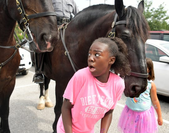 "LOGOS Academy sixth-grader Assata Jones of York City reacts after getting close to Pennsylvania State Police horses Samson, left, and Guffman. during the York City School Police Department Family Fun Festival at York High School Friday, July 27, 2018. The festival is the culmination of the department's 3-week SAFE Camp which, according to its website, offered ""enrichment, educational and athletic opportunities"" programs for youth. Bill Kalina photo"